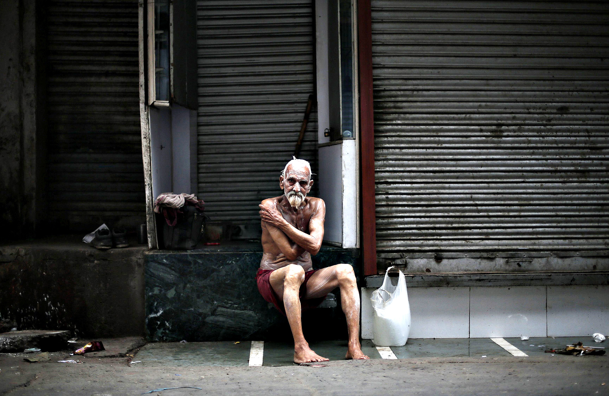 A man bathes in front of closed shops along the roadside in the old quarters of Delhi October 8, 2014.
