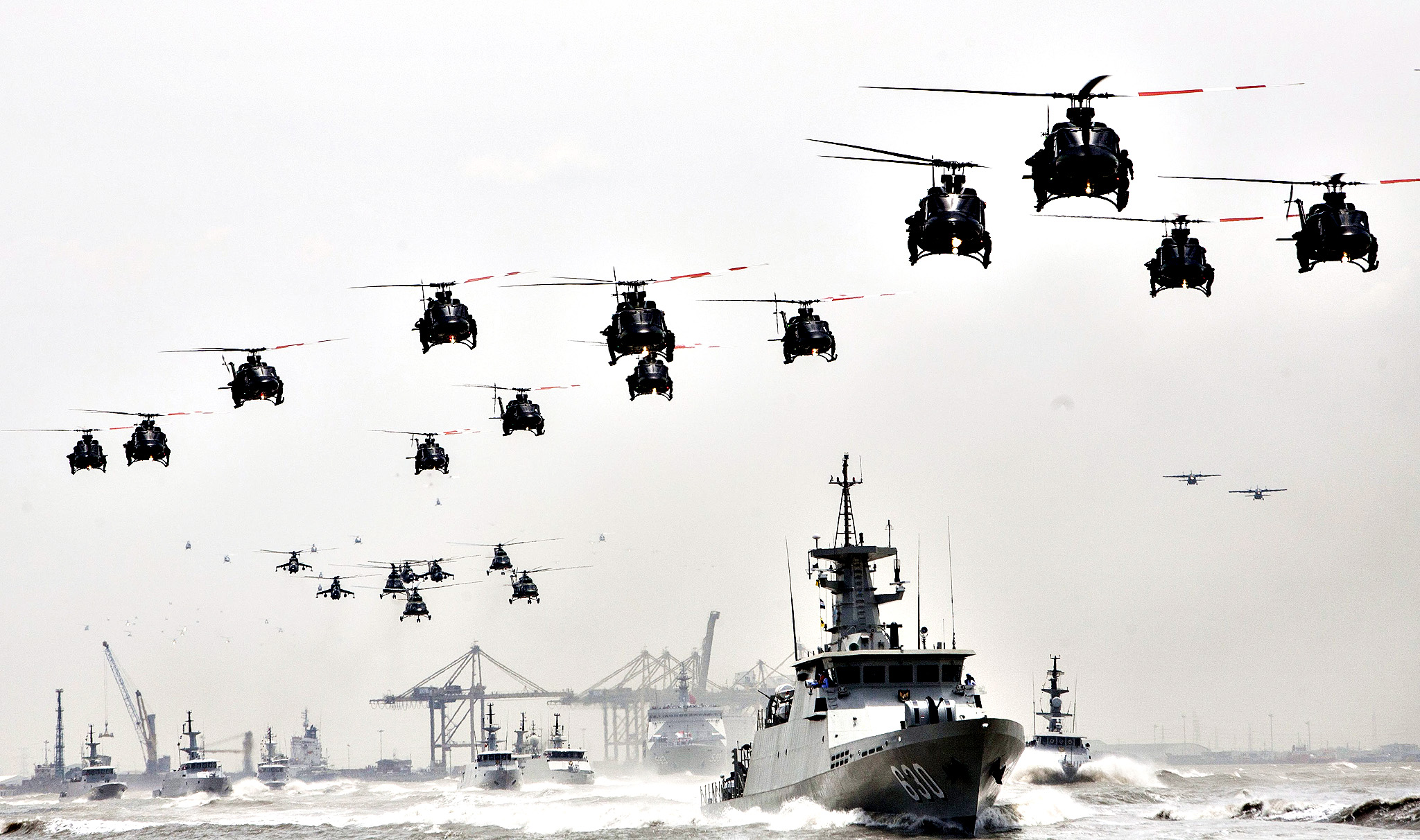 Indonesian Apache helicopter fly in formation over warships during celebrations of the 69th anniversary of the Indonesian Armed Forces (TNI) in Surabaya, East Java, Indonesia, 07 October 2014. More than 20,000 military personnel, 239 units of military aircrafts, 42 units of military ships and 149 units of combat vehicles participated during the celebrations.