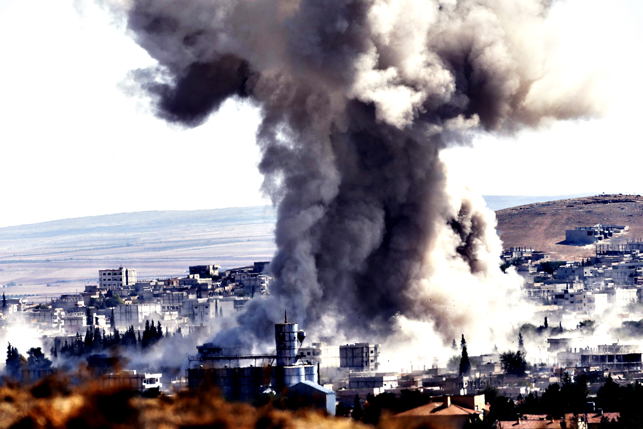 A picture taken from Turkey shows smoke rises after an airstrike by an allegeded alliance war plane on Islamic State targets in the west of Kobane, Syria, where Kurdish fighters YPG are trying to defend the city, near Suruc district, Sanliurfa, Turkey 08 October 2014.  Islamic State militants captured part of a strategic hill overlooking the southern entrance to the besieged Kurdish town of Kobane on Syria's border with Turkey, a monitoring group said. The Islamic State's reported advance came despite what appeared to be the most intense airstrikes yet on jihadist forces around the town by a US-led coalition that formed to fight the militants.