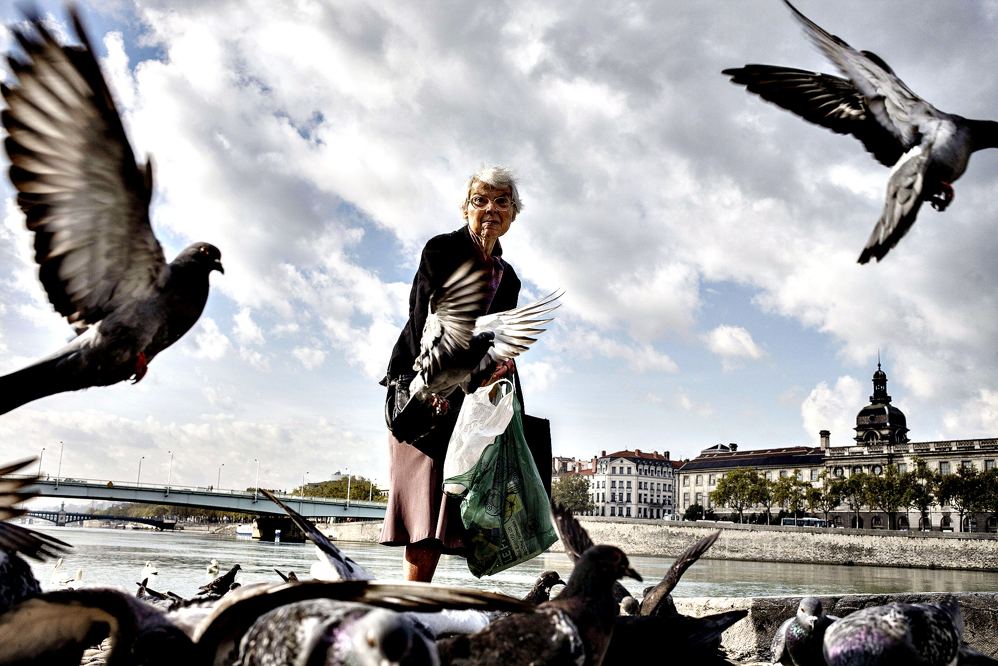 A woman feeds birds on the banks of the Rhone river in Lyon, central-eastern France, on October 23, 2014.