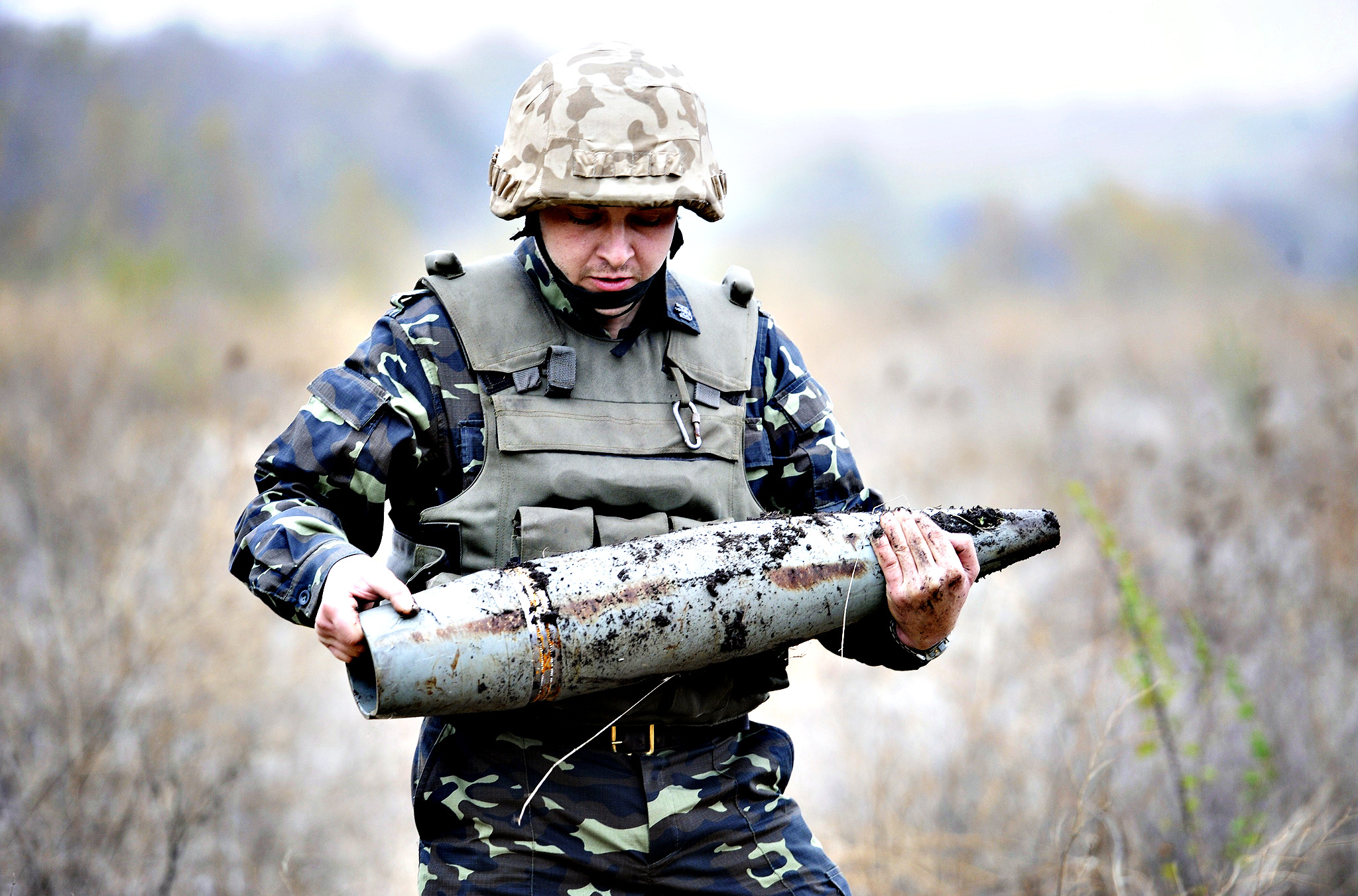 Ukrainian soldier carries an unexploded shell during demining works in a field near the Novoazovsk district in the vicinity of the eastern city of Mariupol on October 23, 2014. As war-weary Ukraine prepares to vote in a snap parliamentary election on October 26, its former master Russia stands by for once apparently unable to influence the outcome. Of the 29 parties running for seats in the 450-seat Verkhovna Rada, the country's parliament, none formally represent the ousted regime of Kremlin-backed Viktor Yanukovych and most support closer ties with the West.