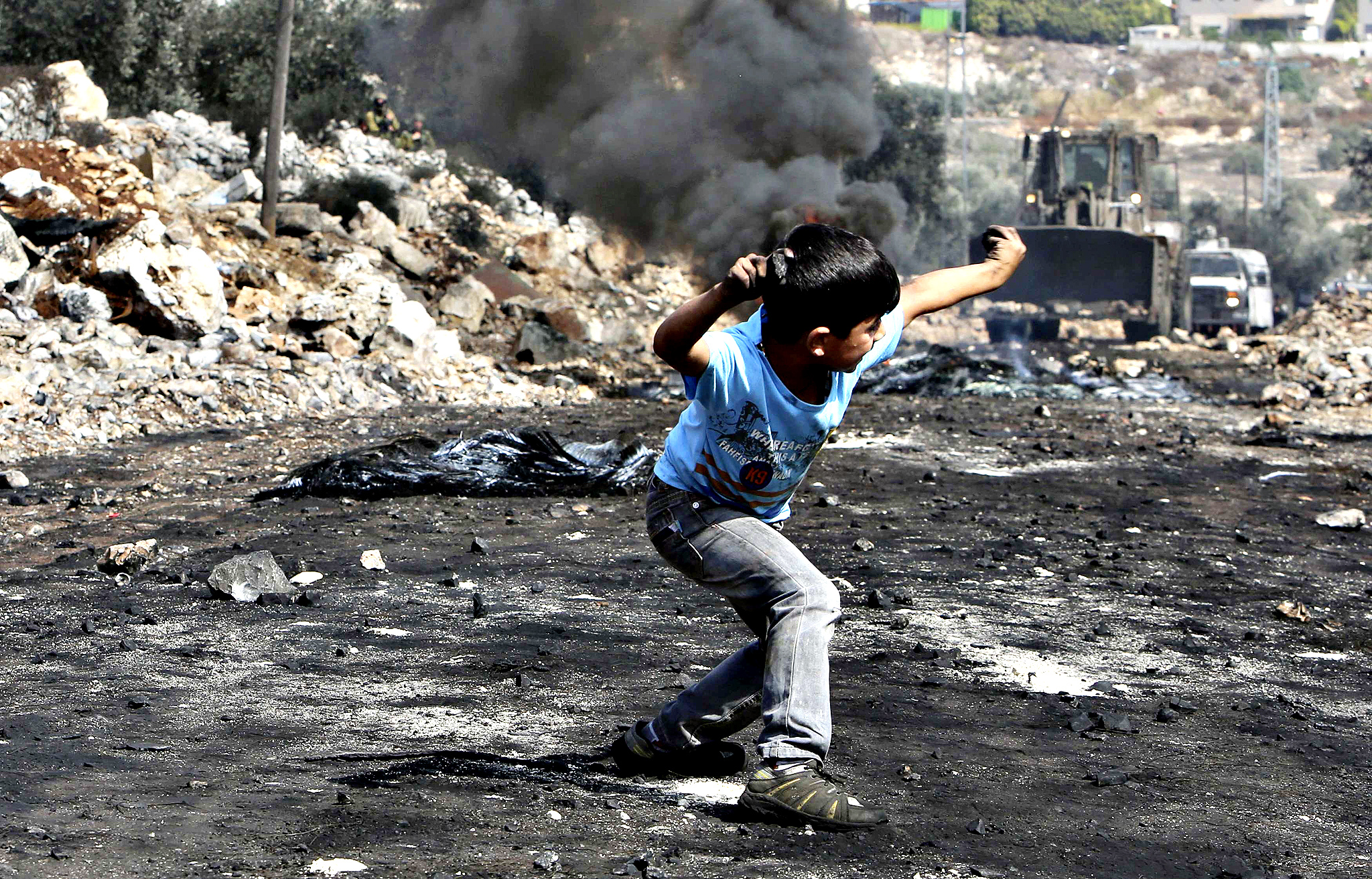 Palestinian boy throws stones at an armored wheel loader of the IDF during clashes following a protest against the near-by Jewish settlement of Qadomem, in the West Bank village of Kofr Qadom...A Palestinian boy throws stones at an armored wheel loader of the Israeli Defense Forces (IDF) during clashes following a protest against the near-by Jewish settlement of Qadomem, in the West Bank village of Kofr Qadom near Nablus October 17, 2014.