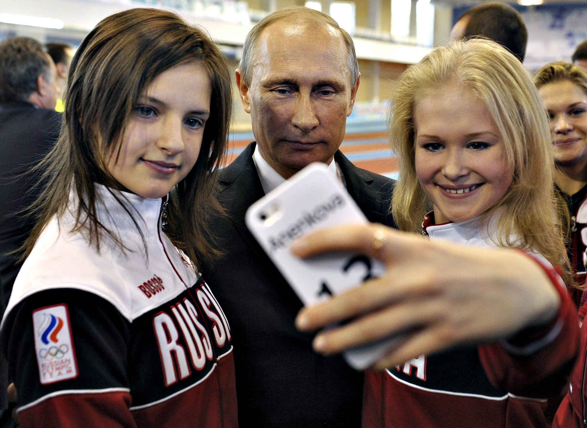 Russian President Putin poses for a picture with youths who took part in the Nanjing 2014 Youth Olympic Games, as he visits a local Olympic youth sports school in Cheboksary...Russian President Vladimir Putin (C) poses for a picture with youths who took part in the Nanjing 2014 Youth Olympic Games, as he visits a local Olympic youth sports school in Cheboksary, October 9, 2014.