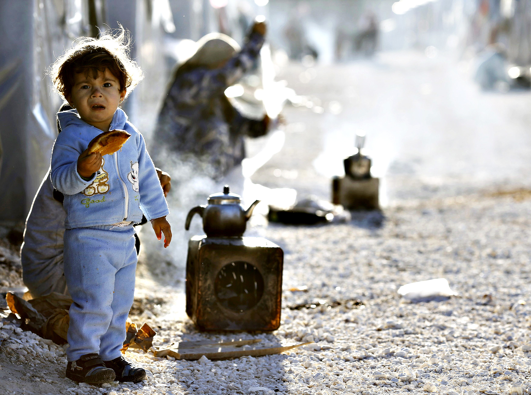 A Kurdish refugee child from the Syrian town of Kobani holds a bread in a camp in the southeastern town of Suruc, Sanliurfa province on October 20, 2014. The U.S. military said it had air-dropped arms to Syrian rebels fighting Islamic State militants near Kobani on Sunday in what appeared to be the Pentagon's first public acknowledgment it has delivered lethal aid to the rebels.