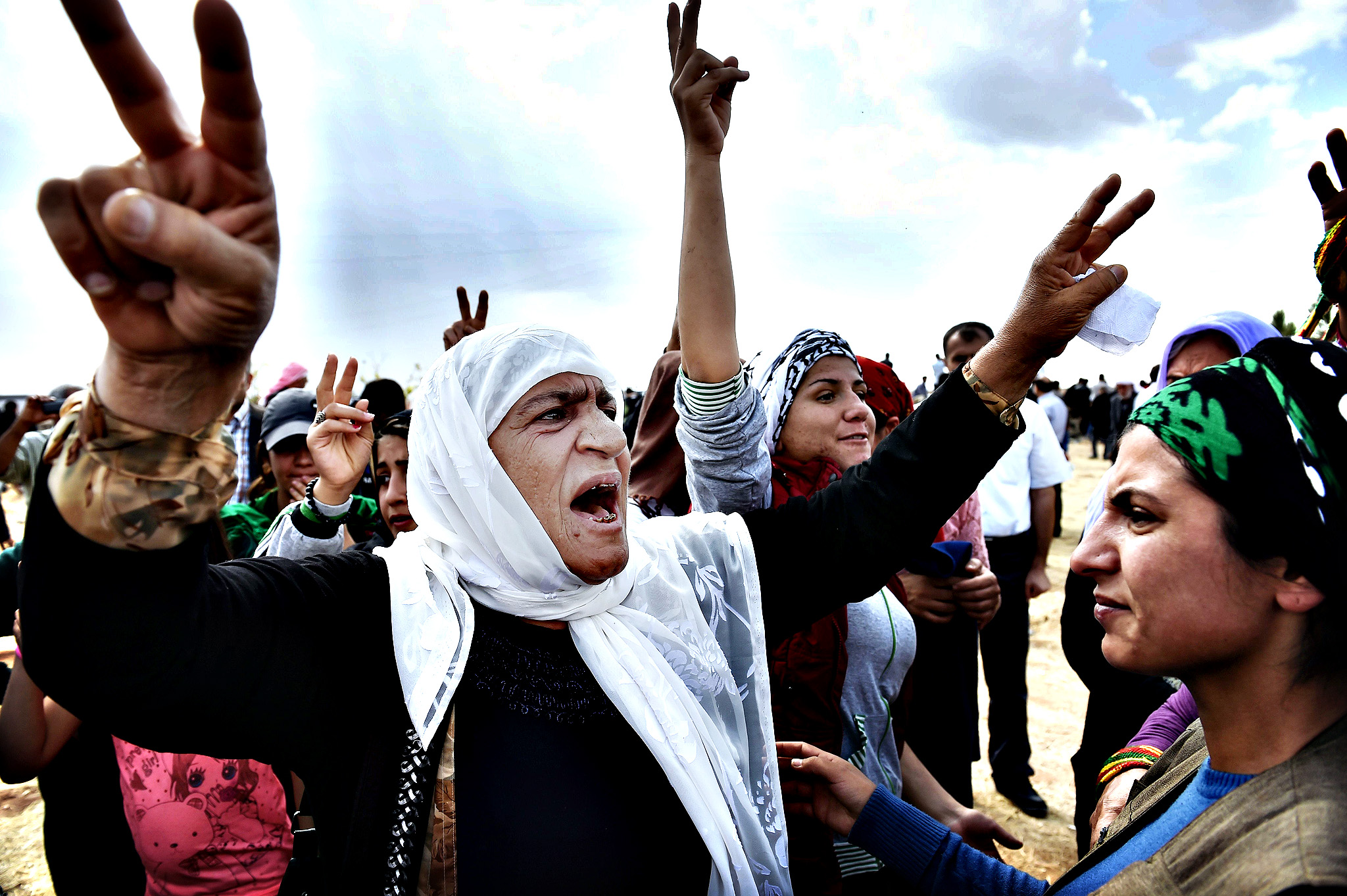 Kurdish women shout slogans during the funeral of a  YPG (People's Protection Units) fighter in the town of Suruc, Sanliurfa province, on October 14, 2014. Attacking Islamic State jihadists met firm Kurdish resistance in the Syrian battleground town of Kobane on Sunday, as neighbouring Turkey heeded pressure to intervene and handed the US access to its air bases.