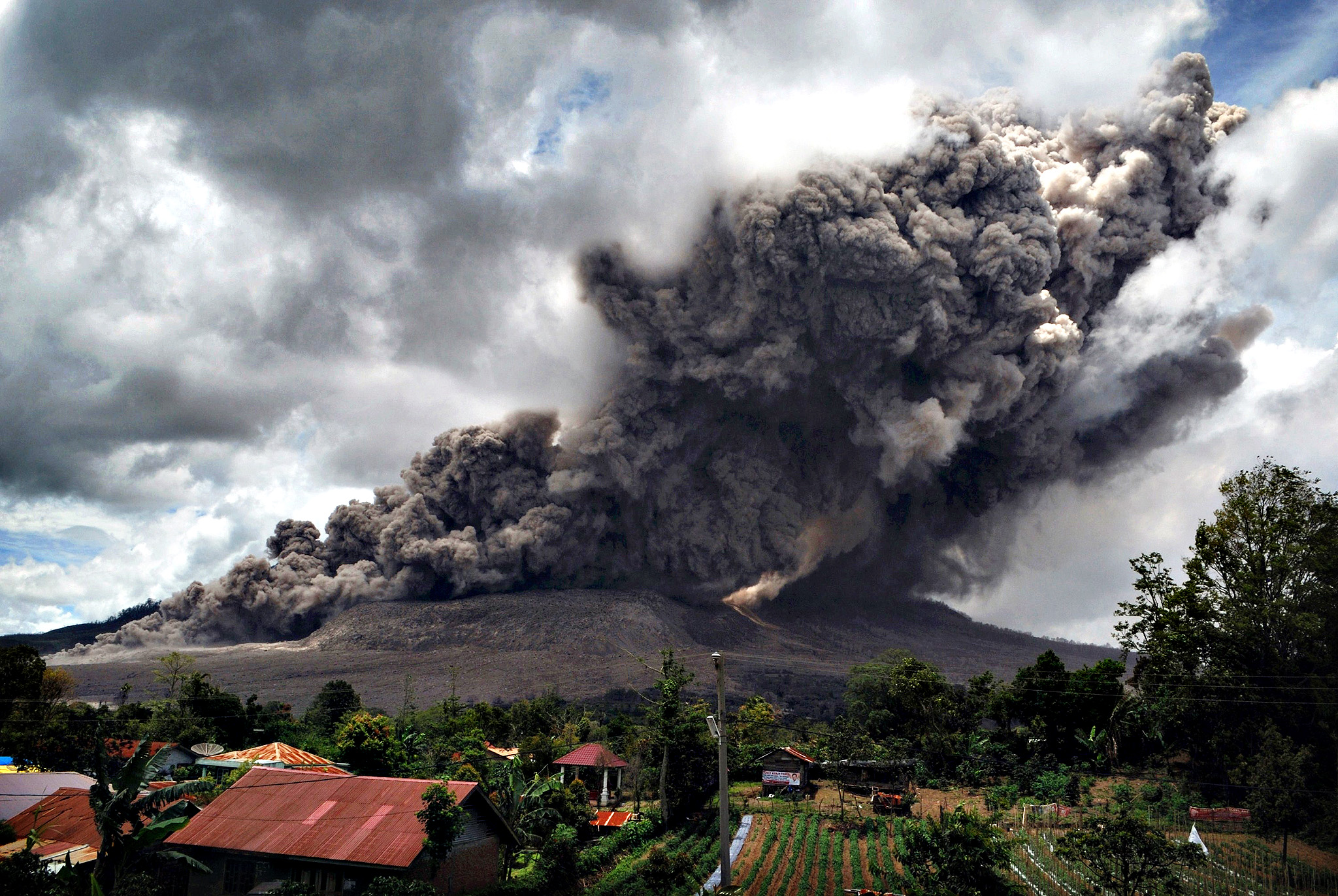 Dark giant ash clouds rise from the crater of Mount Sinabung volcano during an eruption on October 8, 2014, as seen from Karo district located on Indonesia's Sumatra island, following an earlier eruption on October 5, 2014.According to authorities hundreds of residents are still housed at evacuation centers as authorities maintains off limit danger zone around Mount Sinabung located in Indonesia's Sumatra island following deadly eruption in early February that killed about 17 people.