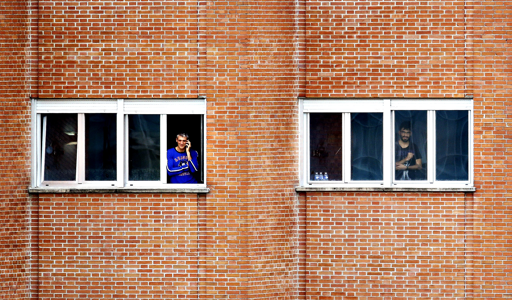 Parra, a doctor who treated Spanish nurse Romero Ramos who contracted Ebola, looks out of a window from his isolation ward at the Carlos III hospital in Madrid...Juan Manuel Parra (L), a doctor who treated Spanish nurse Teresa Romero Ramos who contracted Ebola, looks out of the window of the isolation ward as another unidentified person occupying an adjacent room looks on, at Madrid's Carlos III hospital, October 10, 2014. Seven people turned themselves in late on Thursday to an Ebola isolation unit in Madrid where Teresa Romero, the nurse who became the first person to contract Ebola outside Africa, lay gravely ill.