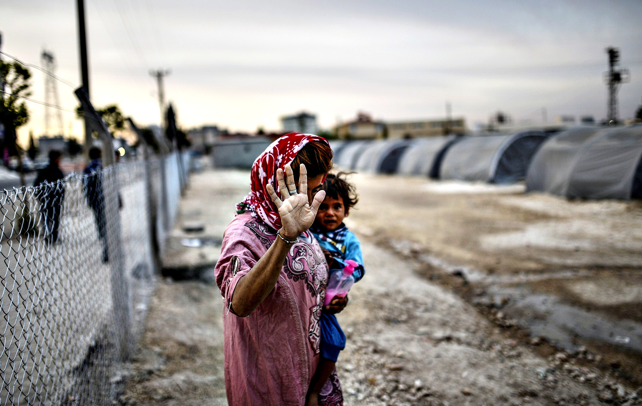 A Syrian Kurdish woman walks with her baby on October 23, 2014,  in the Rojava refugee camp at Suruc in Sanliurfa province. Turkey said on October 21 that Kurdish peshmerga fighters based in Iraq have yet to cross into Syria from Turkish territory, a day after announcing it was assisting their transit to join the battle for the Syrian town of Kobane, also known as Ain al-Arab. It was seen as a major switch in policy by Turkey, which until now has refused to interfere in the over month-long battle for Kobane between Syrian Kurdish fighters and Islamic State (IS) jihadists.