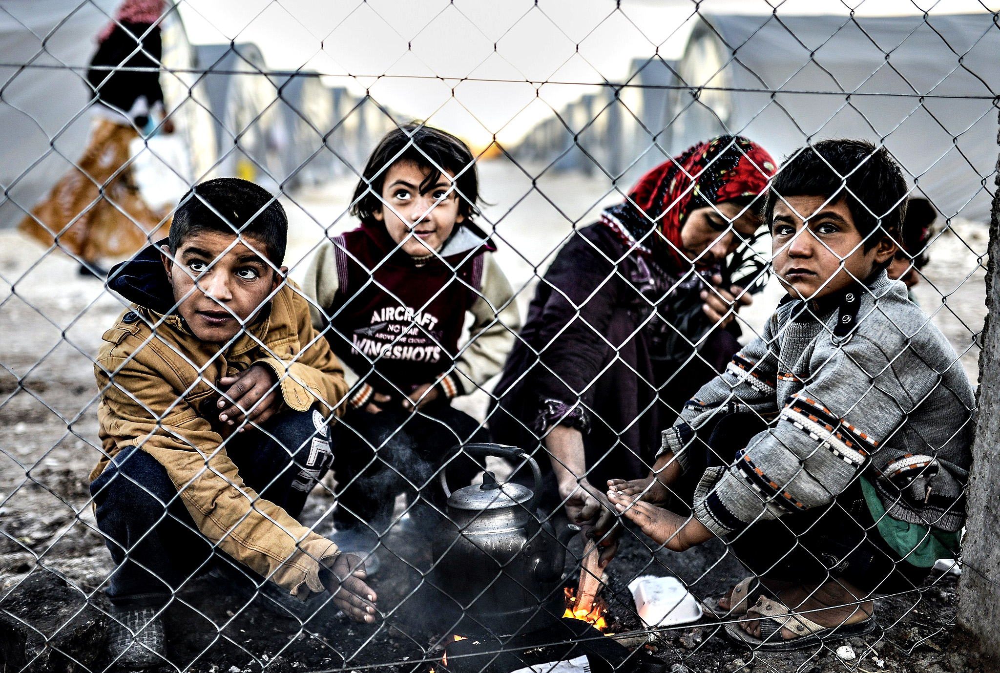 Syrian Kurdish woman and her children gather around a fire early in the morning in a refugee camp at Suruc, in the Sanliurfa province, on October 21, 2014. Turkey dropped its refusal to allow Kurdish fighters over the border to defend the besieged Syrian town of Kobane, saying it was now helping Iraqi peshmerga to cross the frontier in a major policy shift.