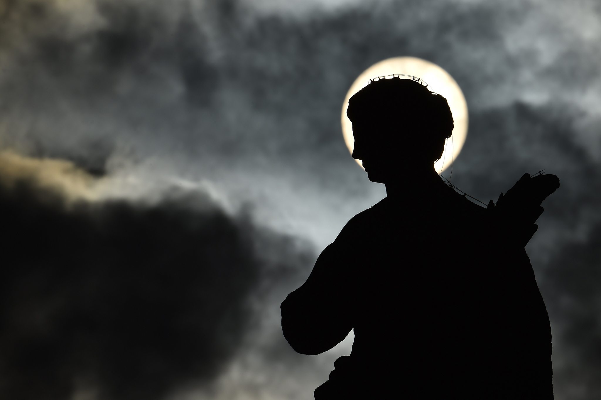 A picture shows the silhouette of a statue at St Peter's square as the sun rises through clouds before a general audience of pope Francis