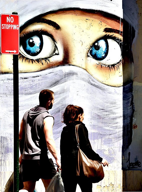 A couple pass in front of a mural of a Muslim woman painted on a wall in an inner city suburb of Sydney on October 2, 2014. Australian military jets are to join in the US-led air war against the Islamic State group in Iraq, conducting refuelling and support missions, Prime Minister Tony Abbott said.
