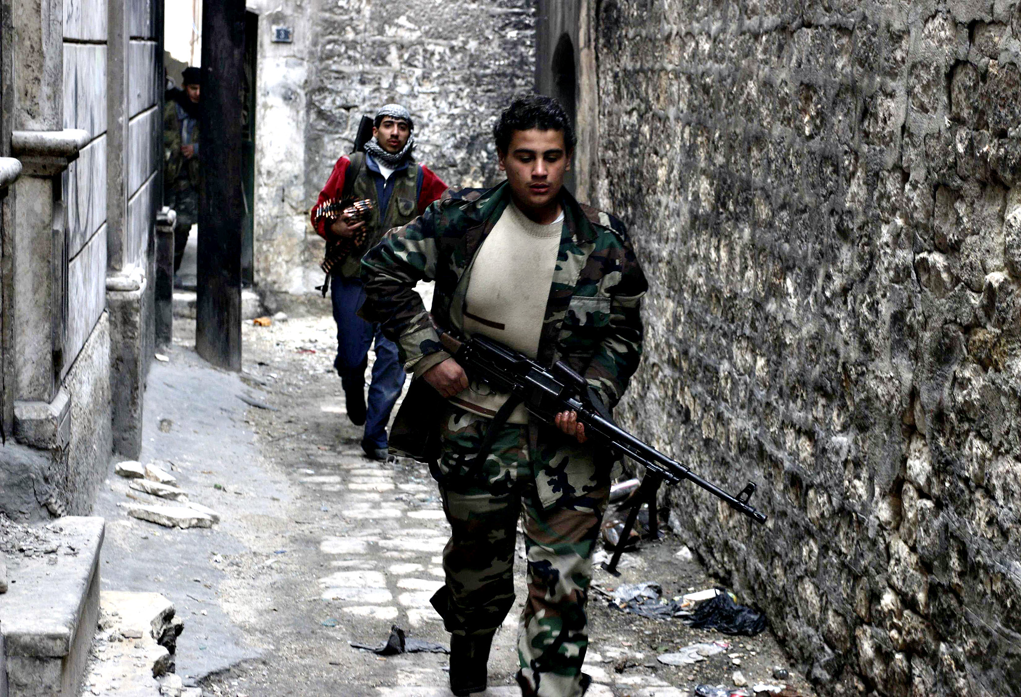 Rebel fighters carry their weapons as they move towards their positions at the frontline against forces loyal to Assad in Maysaloun neighborhood in the old city of Aleppo...Rebel fighters carry their weapons as they move towards their positions at the frontline against forces loyal to Syria's President Bashar al-Assad in Maysaloun neighborhood in the old city of Aleppo November 24, 2014.