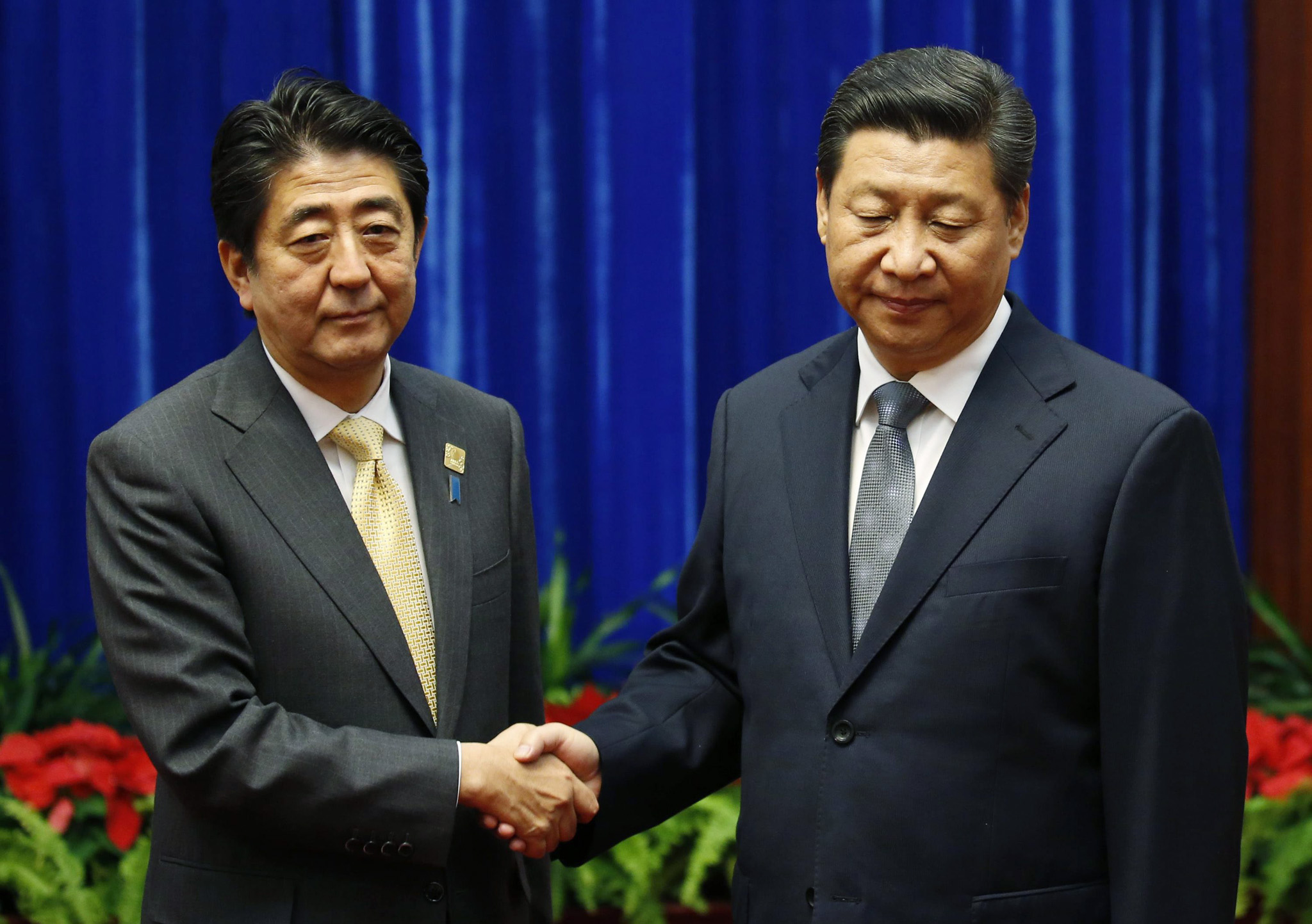 APEC 2014 Summit in Beijing, China...epa04483563 Japan's Prime Minister Shinzo Abe (L) shakes hands with China's President Xi Jinping (R), during their meeting at the Great Hall of the People, on the sidelines of the Asia Pacific Economic Cooperation (APEC) meetings, in Beijing, China, 10 November 2014. APEC is an inter-governmental forum with 21 member countries and regions, that seeks to promote sustainable growth and economic integration, and reduce trade barriers across the Asia-Pacific region. Jinping and Abe met for the first time to face to face talks, since they came into office, on the sidelines of the Asia Pacific Economic Cooperation (APEC) summit in Beijing, China, on 10 November 2014.  EPA/KIM KYUNG-HOON / POOL 0