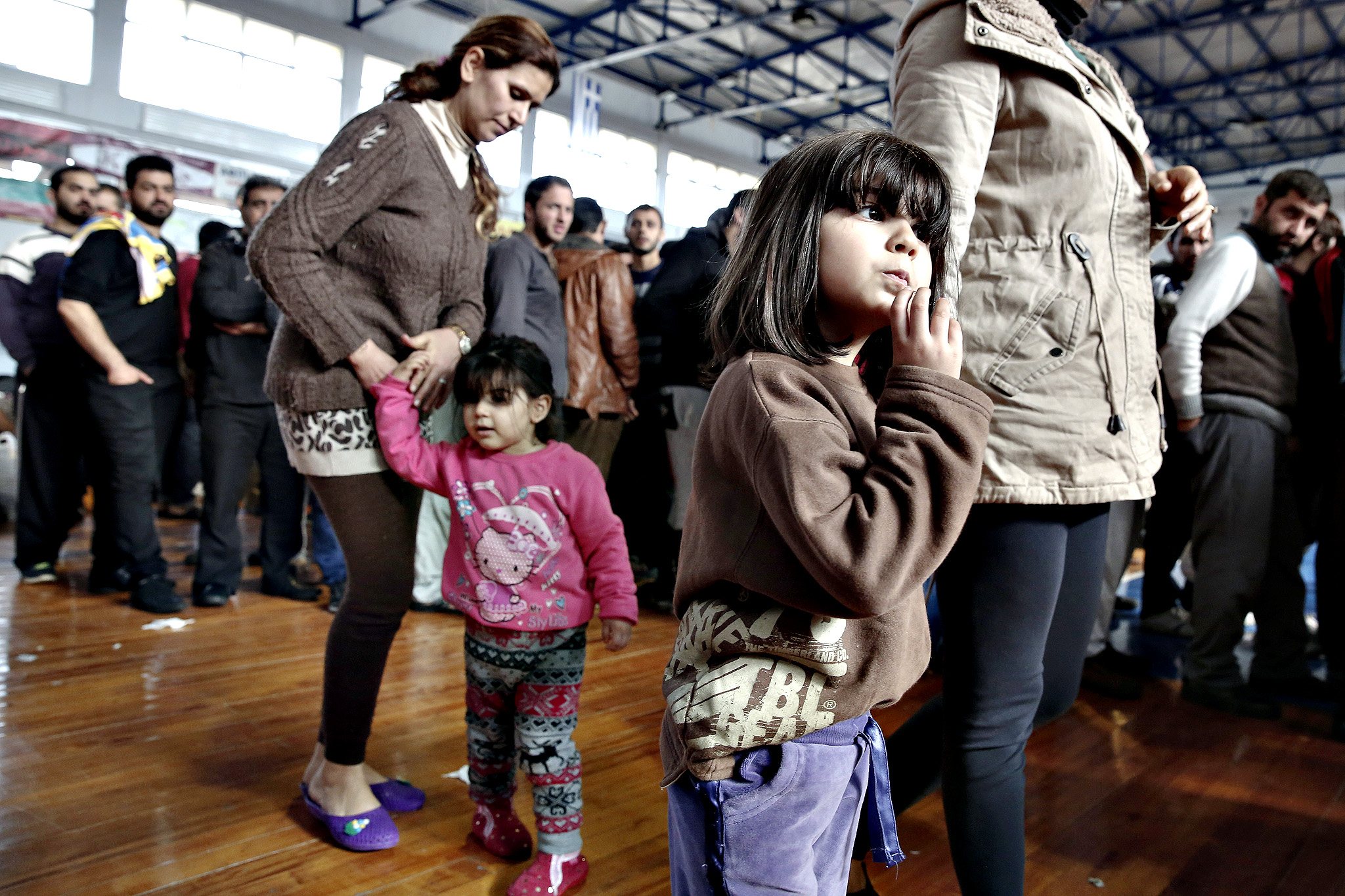Immigrants who arrived on a cargo ship from Turkey queue for meals in a basketball arena where they have been given temporary shelter in the town of Ierapetra, on the southern Greek island of Crete on Friday, Nov. 28, 2014. Nearly 600 men, women and children, mostly refugees from Syria, have been temporarily put up in the southern Cretan town of Ierapetra, where they arrived in a crippled smuggling ship after more than a week at sea.