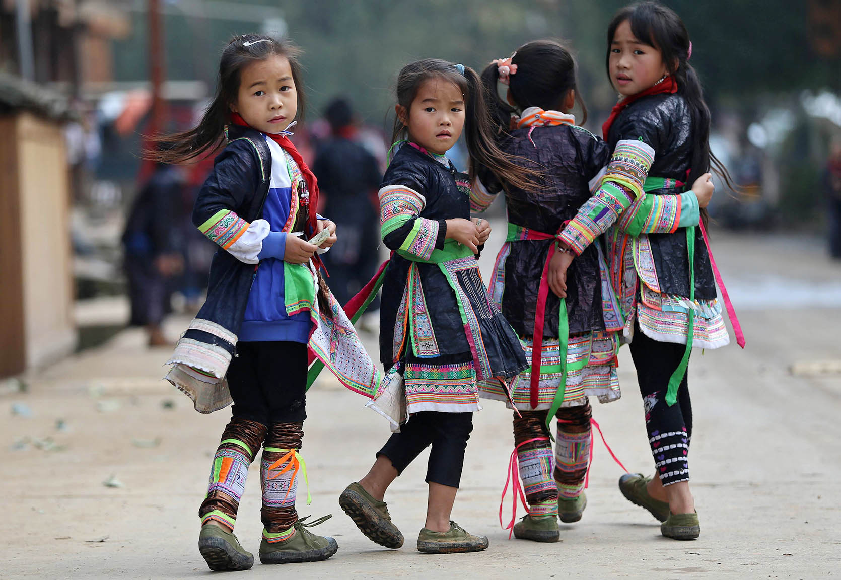 Ethnic Miao girls wearing traditional costumes look back on their way home after school at the village of Basha in Congjiang county