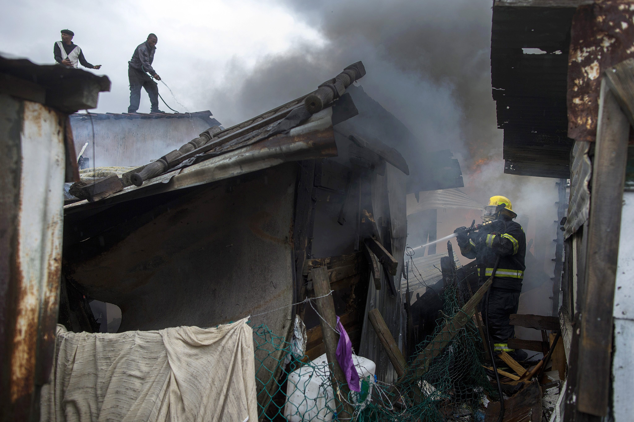 Shack fire in Masiphumelele...epa04474260 South African residents of Masiphumelele assist firemen to extinguish a blaze that devastated parts of the informal shack settlement in Cape Town, South Africa, 03 November 2014. Several shacks were destroyed in the fire which quickly spread in the overpopulated and dense shack settlement. Residents complain of poor access roads for emergency personel who have difficulty getting fire and rescue support to the areas quickly. Inadequate housing and the growing number of informal settlements is one of the major issues facing the government.  EPA/NIC BOTHMA