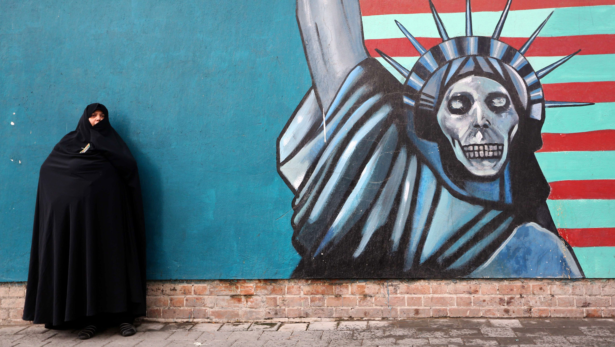 "An Iranian woman stands in front of the painted wall of the former US embassy on November 4, 2014 in Tehran where takes place a demonstration to mark the anniversary of its storming by student protesters that triggered a hostage crisis. Thousands of Iranians shouted ""Death to America"" during the demonstration, 35 years after Islamist students stormed the embassy compound, holding 52 American diplomats hostage for 444 days. The painting shows the Statue of Liberty with a skull as a face."