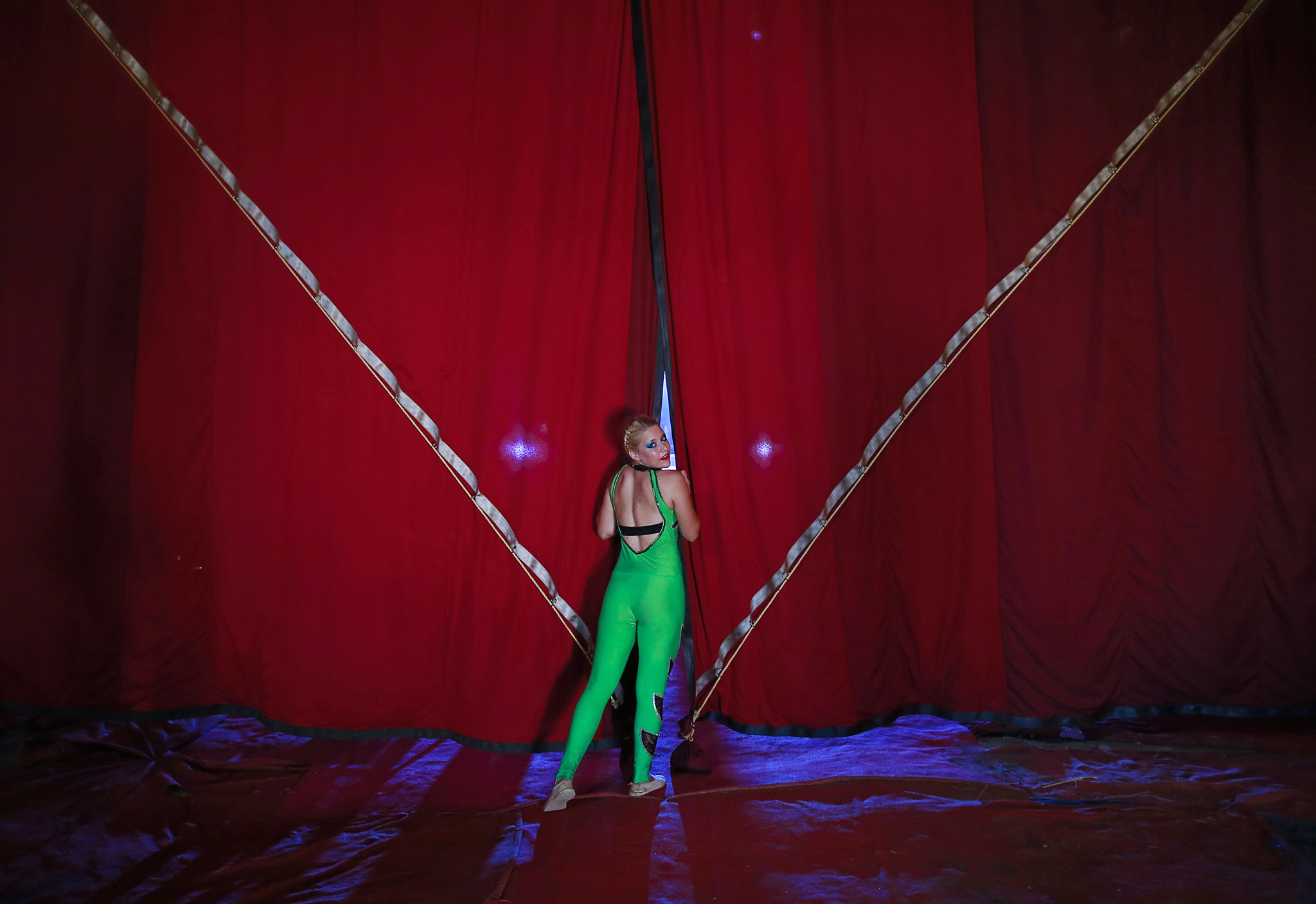 A female member of an acrobatic team looks from behind the curtains as she waits backstage before the start of her performance at the Rambo Circus in Mumbai...A female member of an acrobatic team looks from behind the curtains as she waits backstage before the start of her performance at the Rambo Circus in Mumbai November 6, 2014. The Rambo circus travels all over the country throughout the year. It has a seating capacity of 2,000 people and tickets are priced from 350 rupees ($5.60). According to Rambo Circus owner Sujit Dilip, the ban on the use of wild animals, the lack of new artists and various restrictions by the government have resulted in the drastic decline of the circus industry in India. REUTERS/Danish Siddiqui