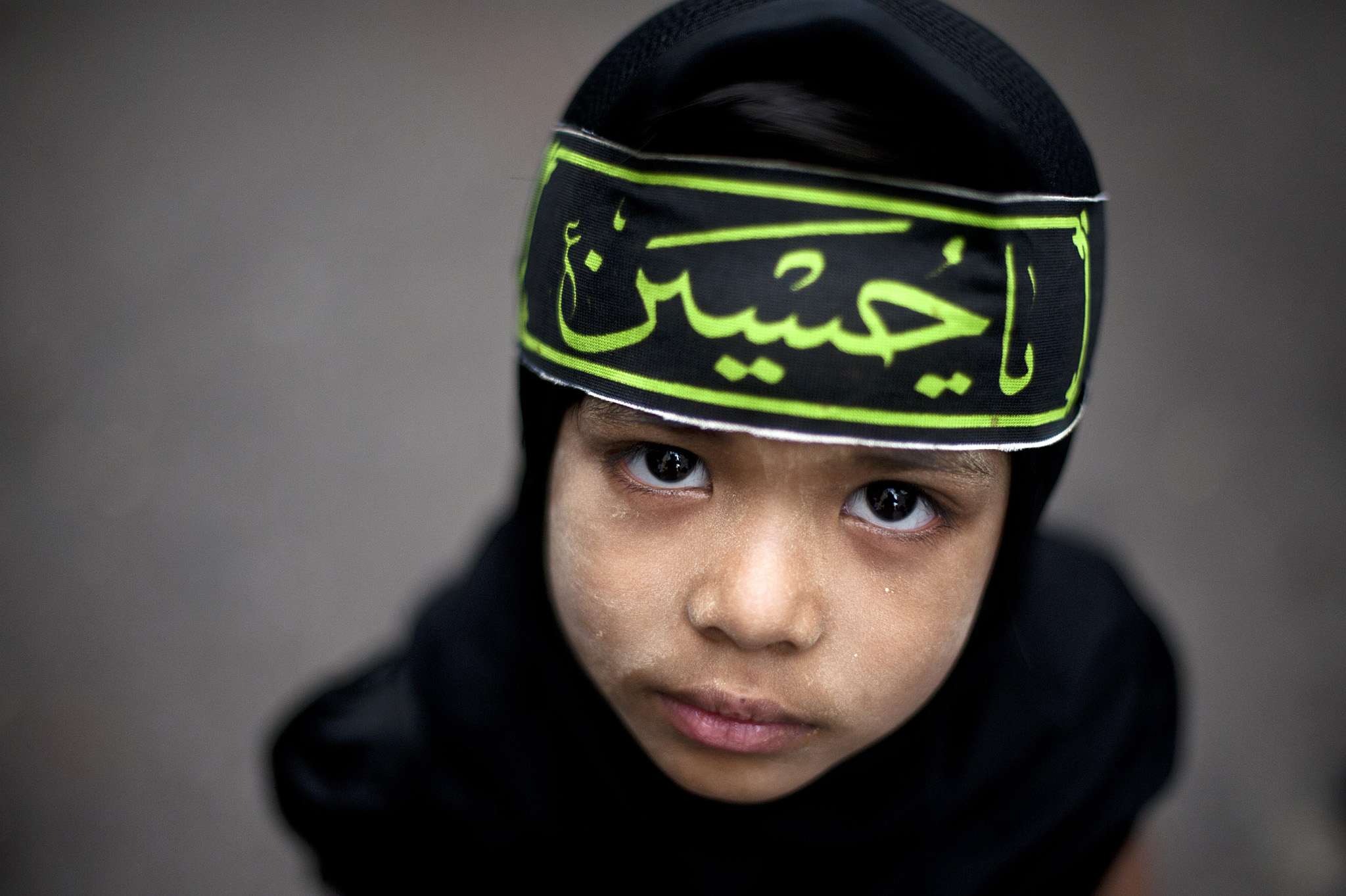 A Myanmar Shiite Muslim child looks up w...A Myanmar Shiite Muslim child looks up while outside a mosque during a procession to mark the Ashura festival in Yangon on November 4, 2014. Ashura marks the peak of 10 days of mourning for the death of Imam Hussein, one of the most revered figures in Shiite Islam.     AFP PHOTO / Ye Aung THUYe Aung Thu/AFP/Getty Images