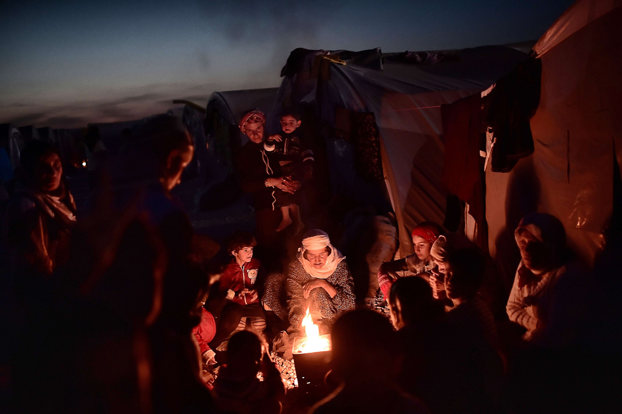 TOPSHOTS Syrian Kurdish refugees gather ...TOPSHOTS Syrian Kurdish refugees gather around fire in a refugee camp in Suruc, Sanliurfa province, on November 11