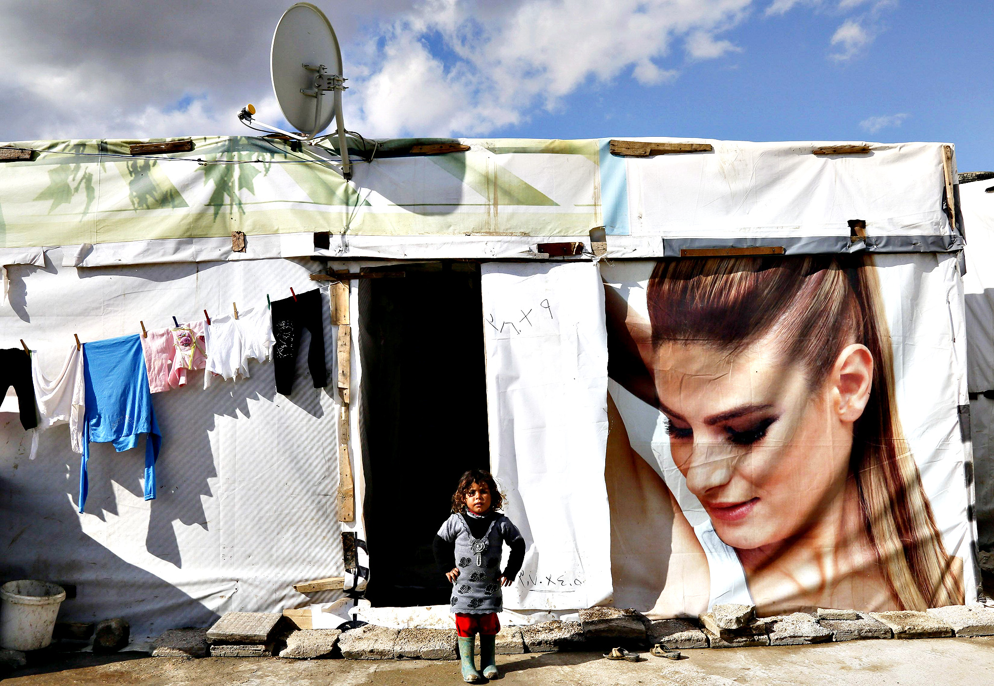 A Syrian refugee girl stands near her tent at a refugee camp in Zahle in the Bekaa valley November 27, 2014.