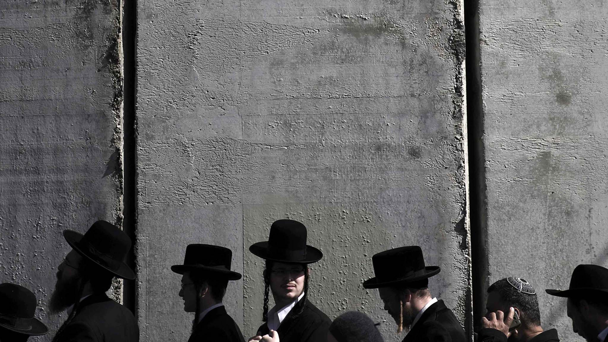 Ultra-Orthodox Jewish men walk near the controversial Israeli barrier outside Rachel's tomb in Bethlehem