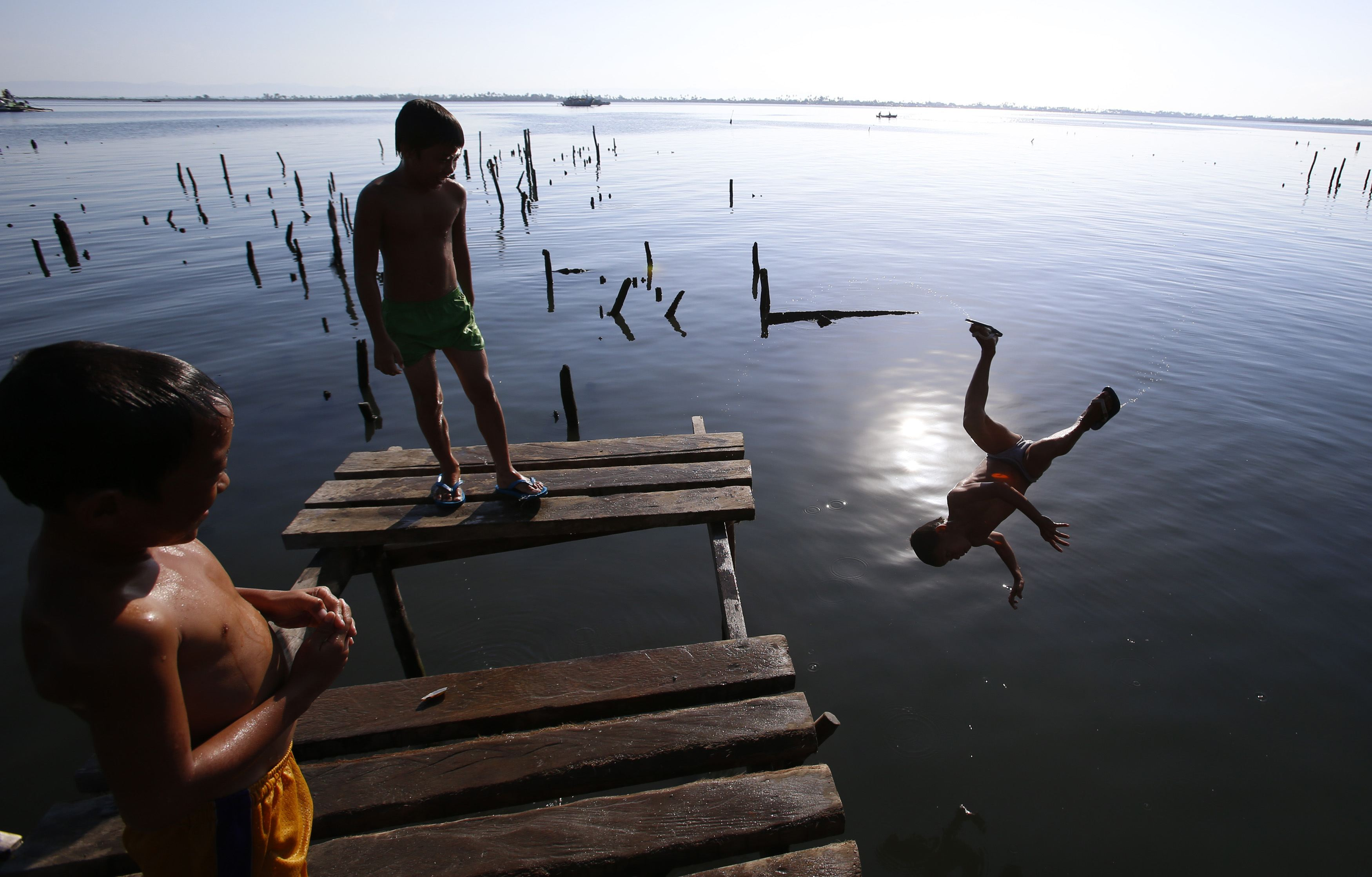 Boys jump from a cut-off foot bridge, which was damaged by Typhoon Haiyan, at a typhoon devastated coastal village in Tacloban city in central Philippines November 7, 2014. Almost 25,000 people still live in tents, shelters and bunkhouses in the hardest hit regions in central Philippines, including Tacloban City, considered Haiyan's ground zero as it accounted for almost half of the death toll. The Philippines are preparing to commemorate victims of Typhoon Haiyan, ahead of the one-year anniversary of the disaster on November 8, according to a government official