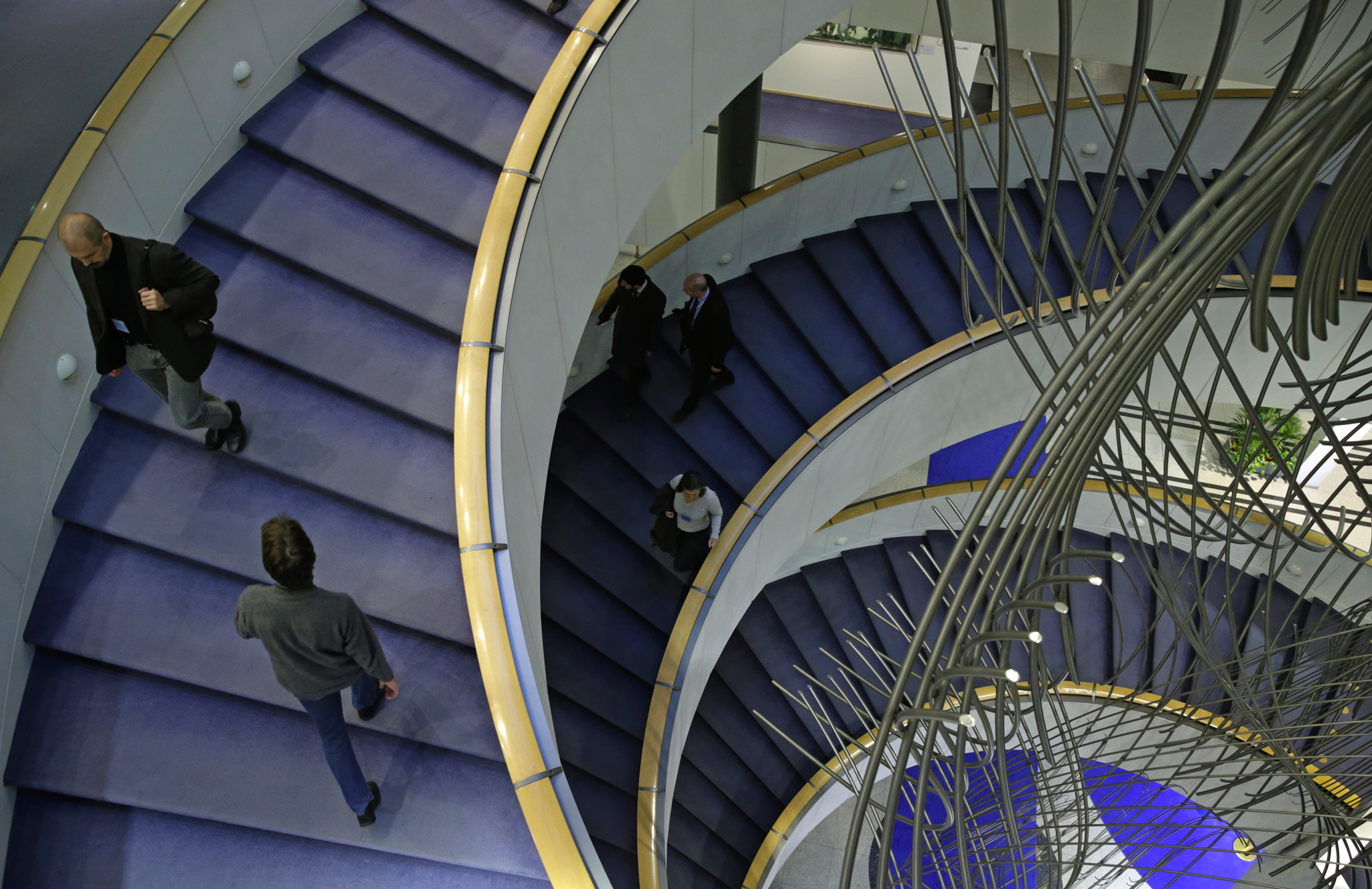 People walk the stairs of the European Parliament building, in Brussels.
