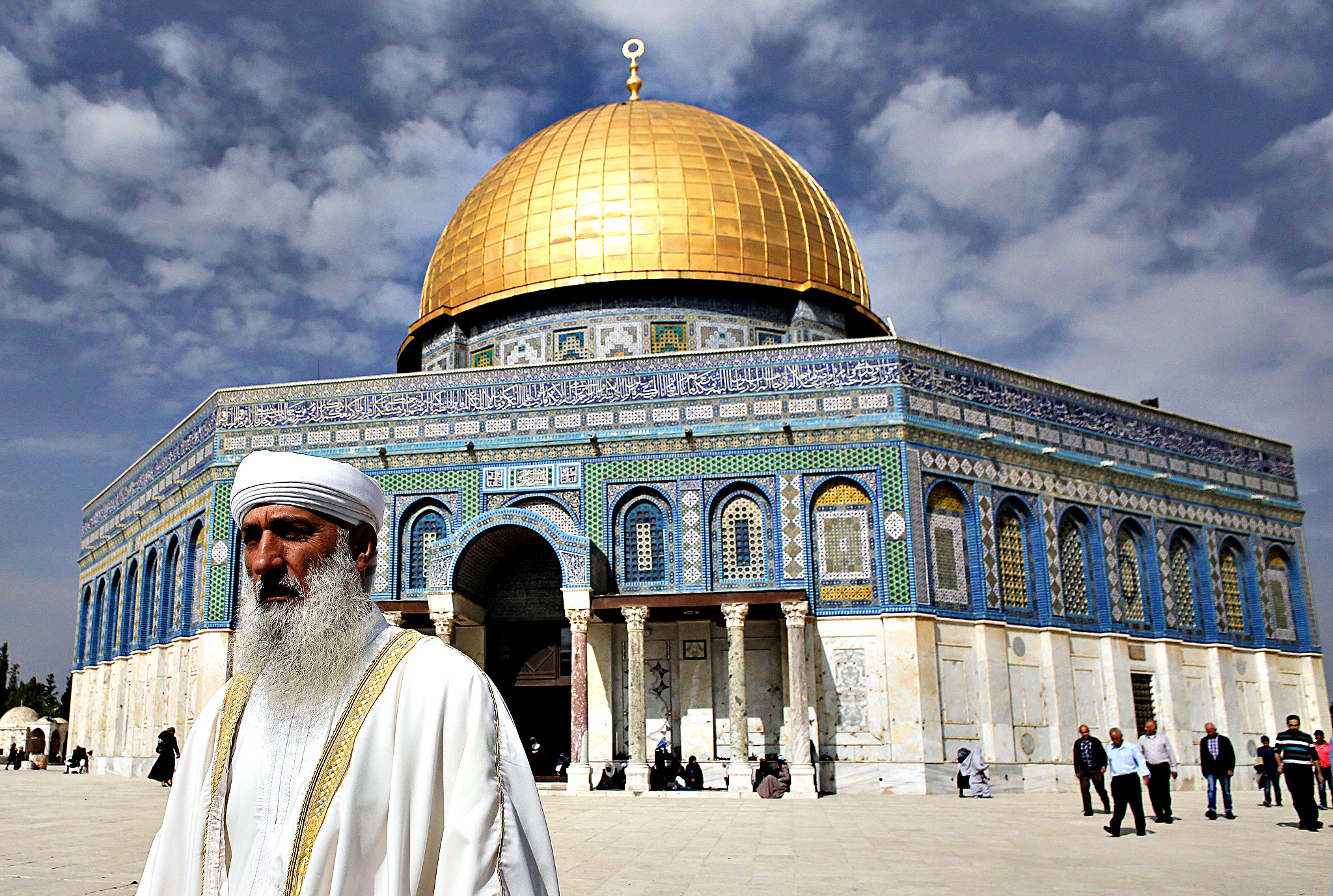Palestinian worshippers walk outside the Dome of the Rock at the Al-Aqsa mosque compound after Friday prayers  in the Old City of Jerusalem on November 14, 2014. Israel eased restrictions at Jerusalem's Al-Aqsa mosque after US Secretary of State John Kerry announced agreement on steps to reduce tensions at the flashpoint compound.