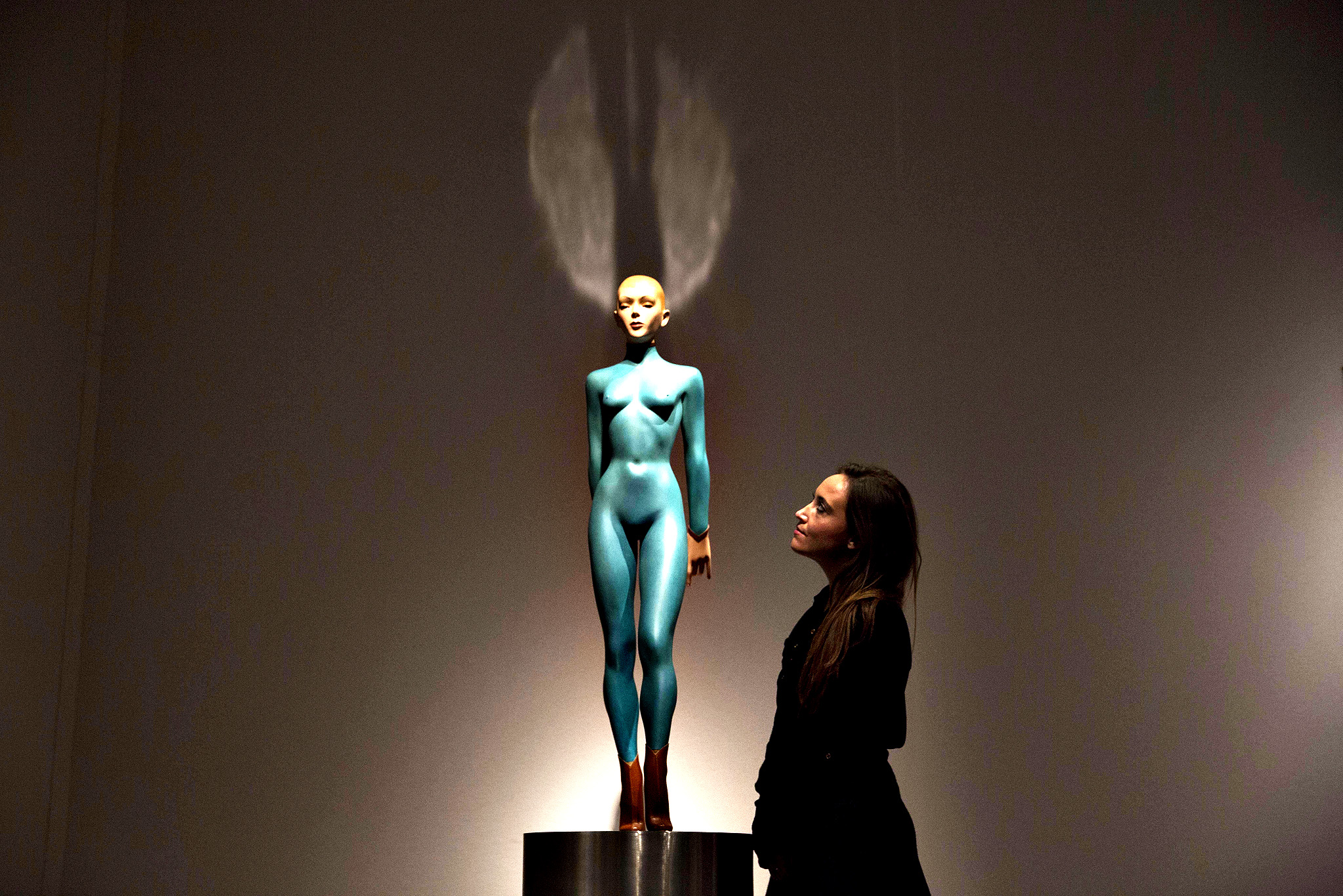 "An employee of the Christie's auction house poses for photographs beside the Allen Jones sculpture ""Enchanteresse"", painted bronze and leather on a steel base at their premises in London, Monday, Nov. 17, 2014.  The piece is estimated to fetch 60,000 to 80,000 pounds ($93,870 to $125,160, / 75,122 to 100,163 euro), when it features in a Modern British and Irish Art evening sale in London on November 19."