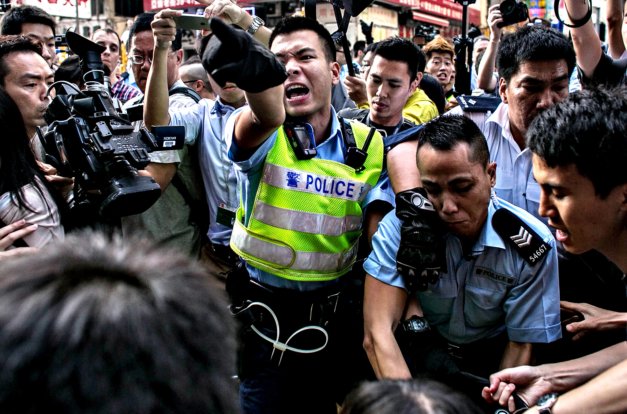 Police clash with protesters as they try to clear the street after agents authorized by bailiff's removed barricades on Argyle Street in Mongkok district on November 25, 2014 in Hong Kong. The Mong Kok protest site is scheduled for clearance by baliffs this week after Hong Kong's high court authorized police to arrest protesters who obstruct bailiffs on the three interim restraining orders.