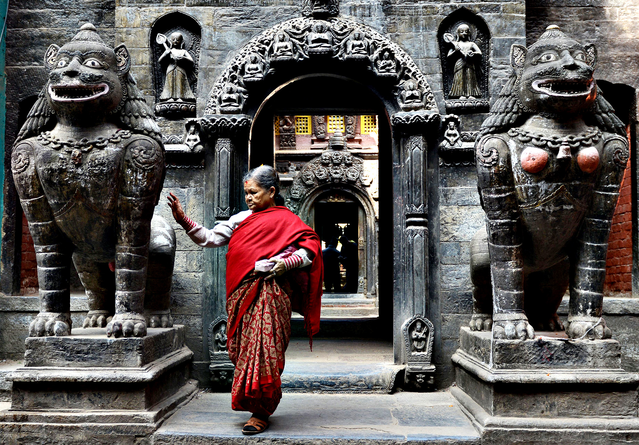 A Nepalese Buddhist devotee leaves after offering prayers at the Golden Temple near Patan Durbar square in Lalitpur, about five kilometers south-east of Kathmandu on November 3, 2014. The Golden Temple was founded during the 12th Century near Patan Durbar Square, a UNESCO World Heritage site, famous for fine ancient art, making of metallic and stone carving statues.