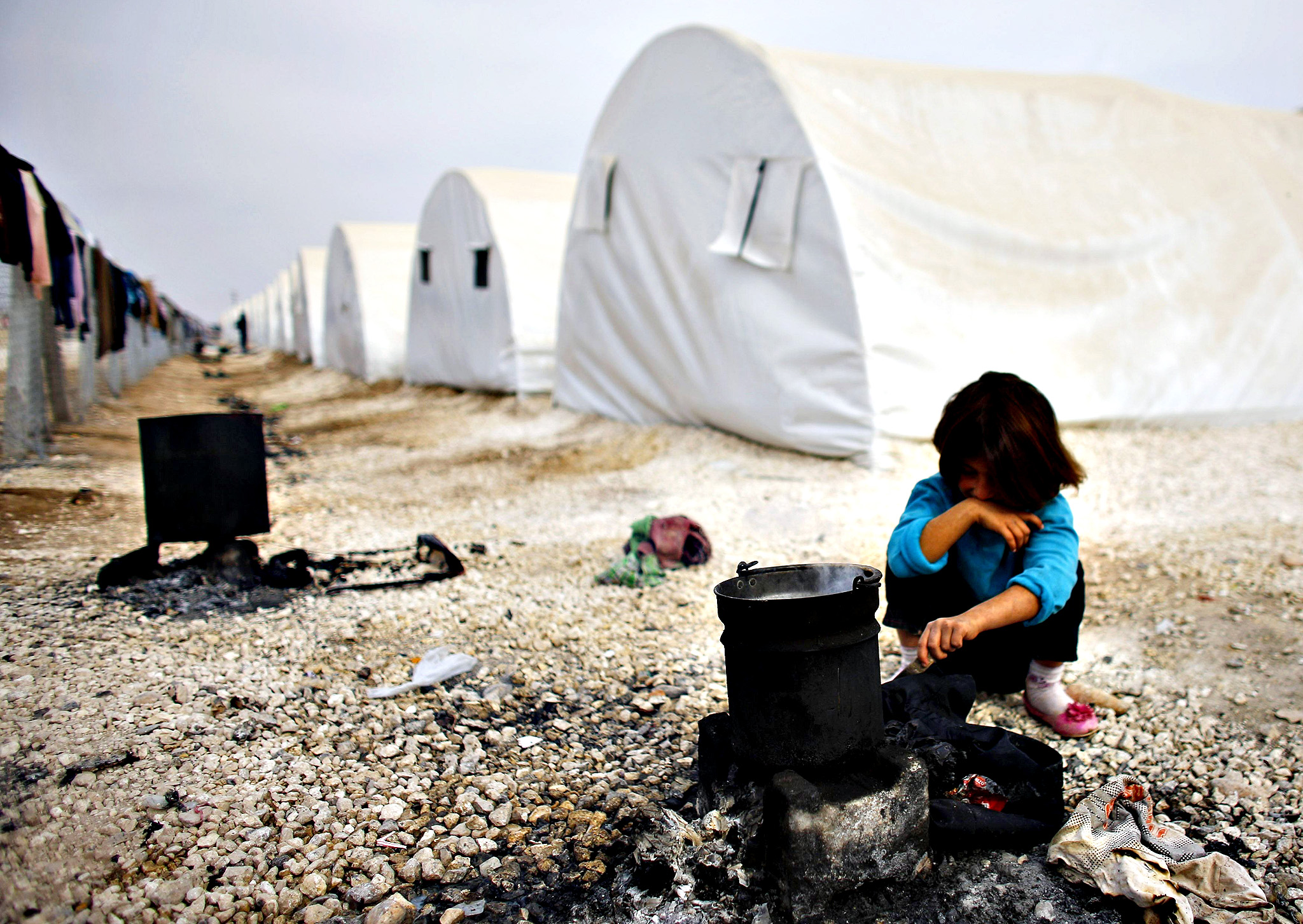 Young girl cooking on a fire pit in a row of tents in a Syrian refugee camp.