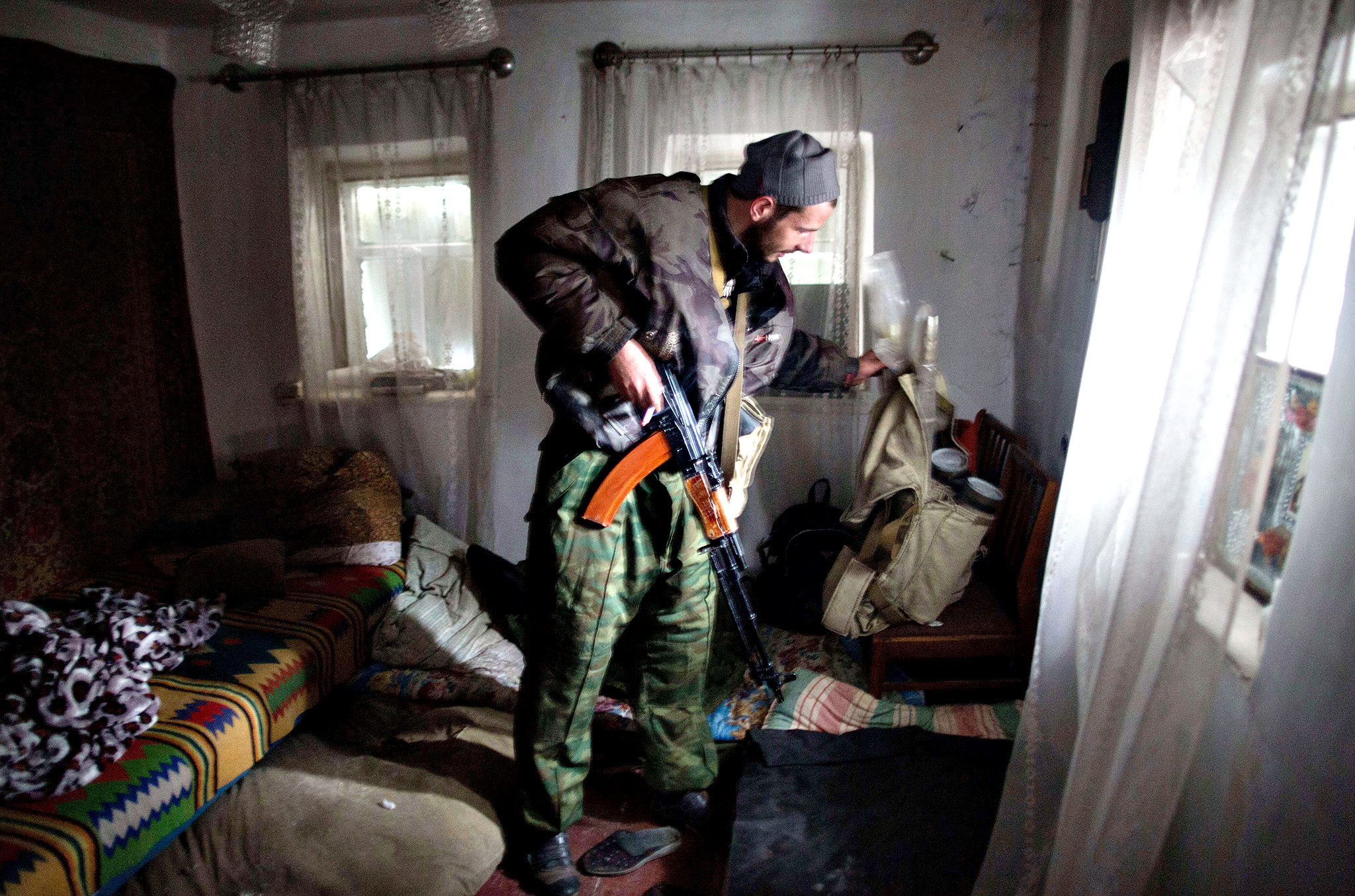 A Pro-Russian gunman prepares in his room in the Oktyaber neighborhood, north west of Donetsk, near the destroyed airport, on November 13, 2014, following last days shelling in eastern Ukraine. After NATO accused Russia of deploying tanks, troops and military hardware to the region, Ukraine said on November 13, four of its soldiers had been killed in the past 24 hours and 18 wounded.