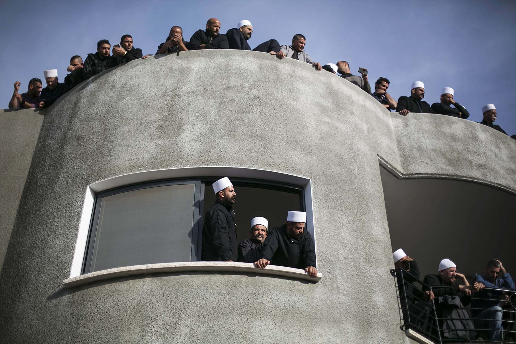Members of the Druze community watch the funeral of Israeli Druze police officer Zidan Nahad Seif in Yanuh-Jat