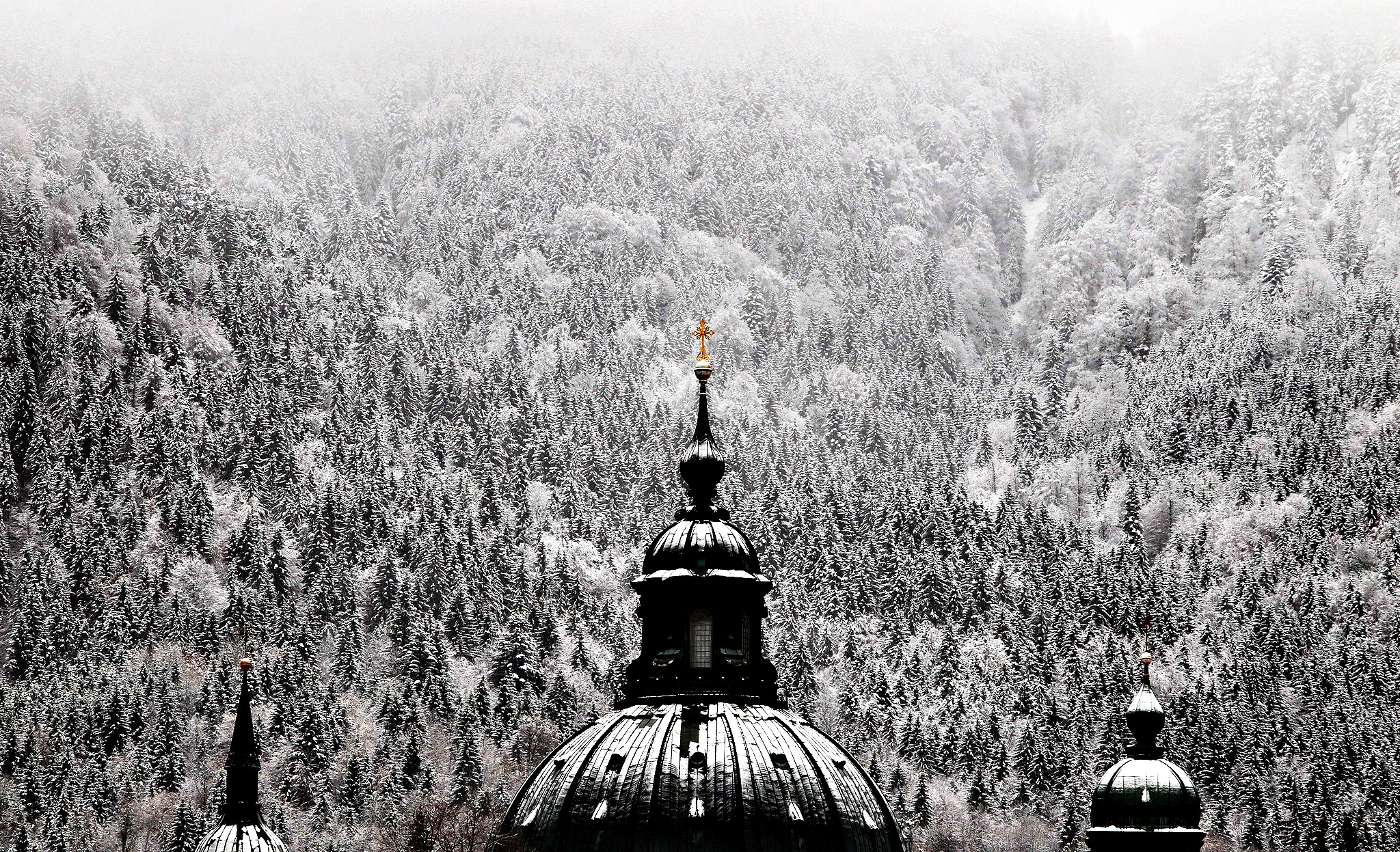 A tower of Ettal Abbey is seen in front of the snow-covered landscape on November 18, 2014 in Ettal, southern Germany.