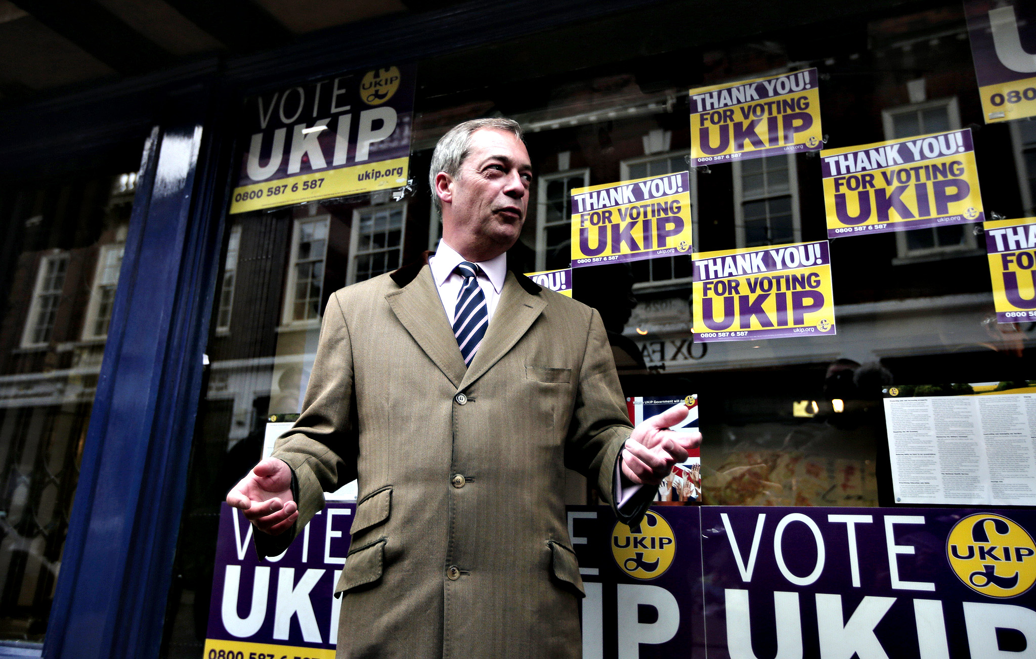 Nigel Farage, the leader of the U.K. Independence Party (UKIP) poses for photographers in front of the party's offices in Rochester, England, Friday, Nov. 21, 2014, a day after a special election. UKIP, Britain's anti-immigration party, UKIP, has easily won its second seat in parliament as Mark Reckless,  a former Conservative lawmaker ran well ahead of his old party. Reckless, the second Conservative to leave the party and win a seat for UKIP, won 42 percent of the vote in a special election in the Rochester & Strood constituency in southeast England.