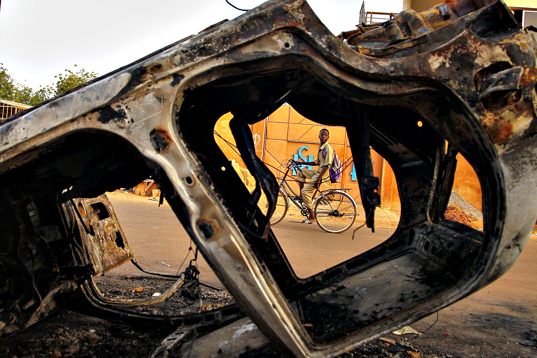 A boy from Burkina Faso cycles past burned vehicles damaged during violent demonstrations by pro democracy protesters that led to the resignation of President Blaise Compaore in Ouagadougou, Burkina Faso, 03 November 2014. President Blaise Compaore resigned on 31 October 2014 following the violent protests against his bid to change the constitution to extend his rule of 27 years. After a brief claim to power by army General Honore Traore a power struggle ensued with Presidential guard commander Lieutenat-Colonel Isaac Zide being appointed as transitional leader. Thousands of protesters took to the Place de la Nation on 02 November in protest against the military rule.