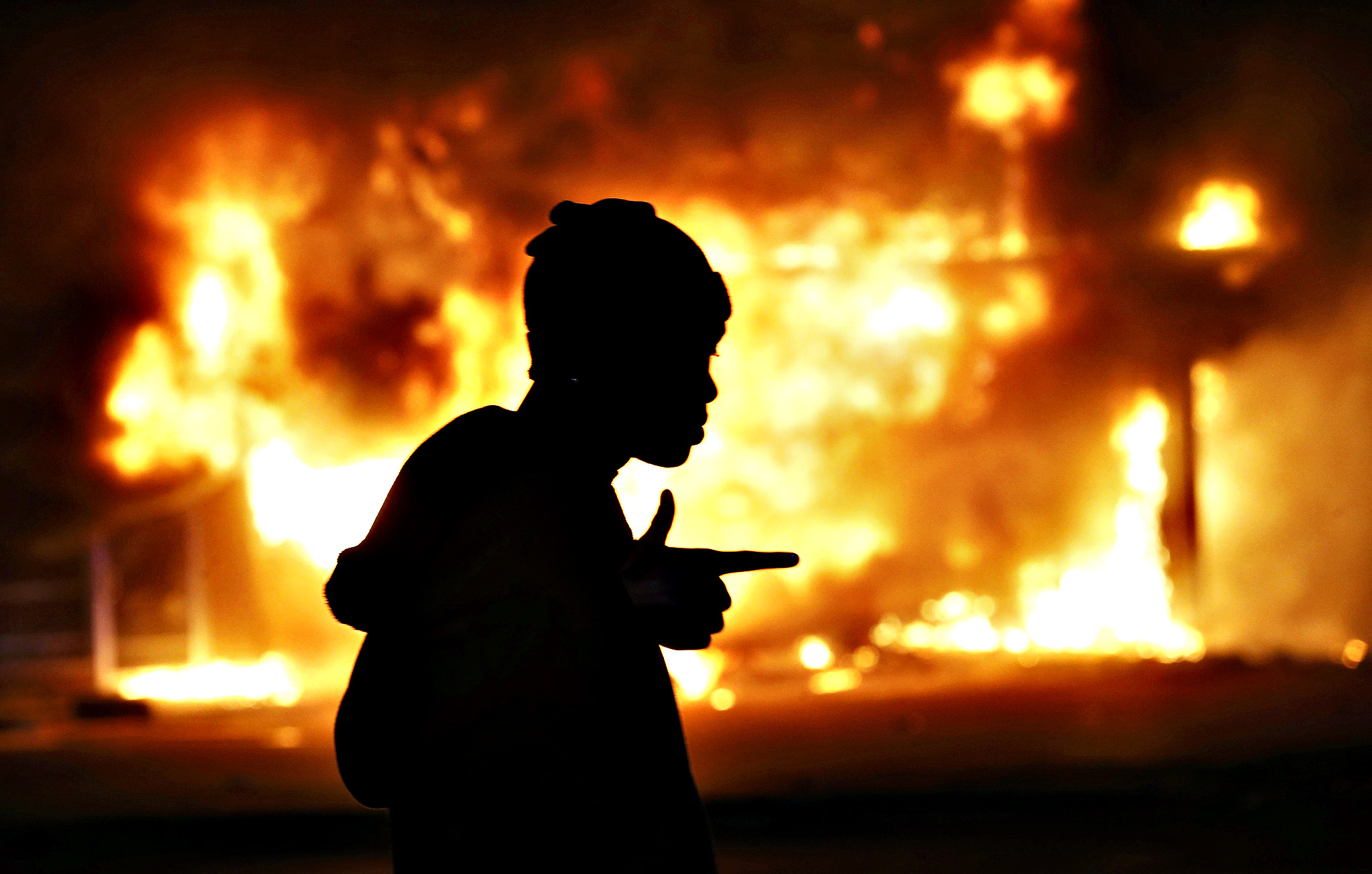 A man walks past a burning building during rioting after a grand jury returned no indictment in the shooting of Michael Brown in Ferguson, Missouri November 24, 2014. Gunshots were heard and bottles were thrown as anger rippled through a crowd outside the Ferguson Police Department in suburban St. Louis after authorities on Monday announced that a grand jury voted not to indict a white officer in the August shooting death of an unarmed black teen.