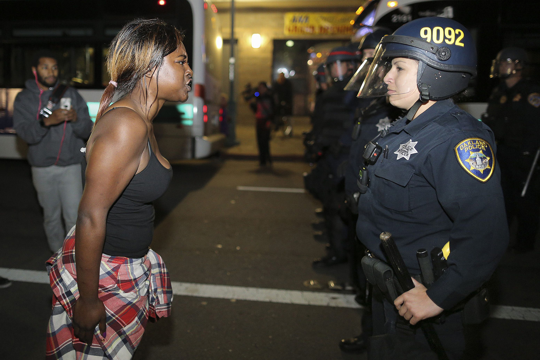 Amanda Ashe of Oakland faces off with a police officer during a demonstration in Oakland, California
