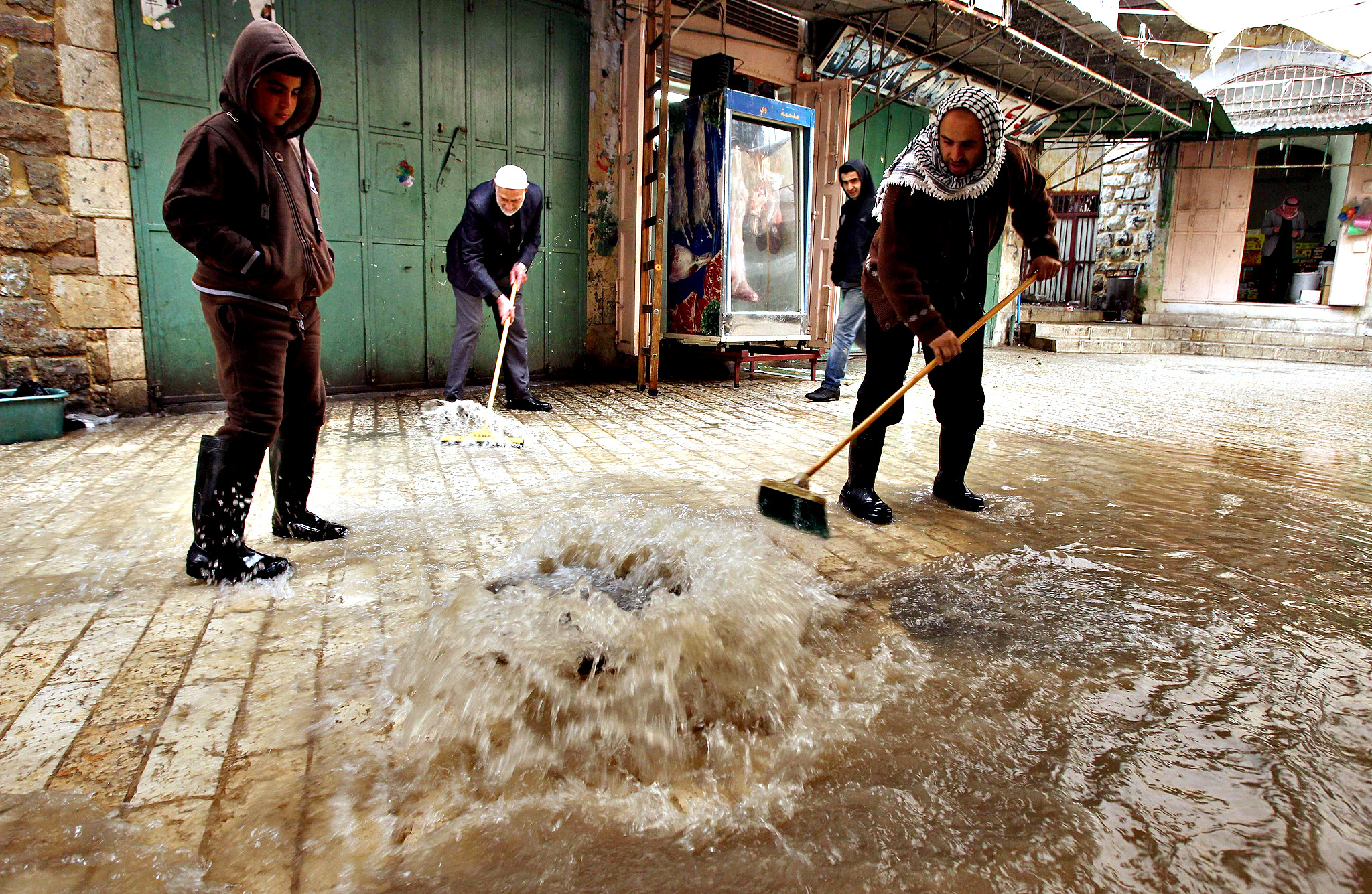Palestinian men try to prevent flood water from entering shops in the old city of Hebron on November 27, 2014 as a fierce winter storm which has been battering the region for the past four days.