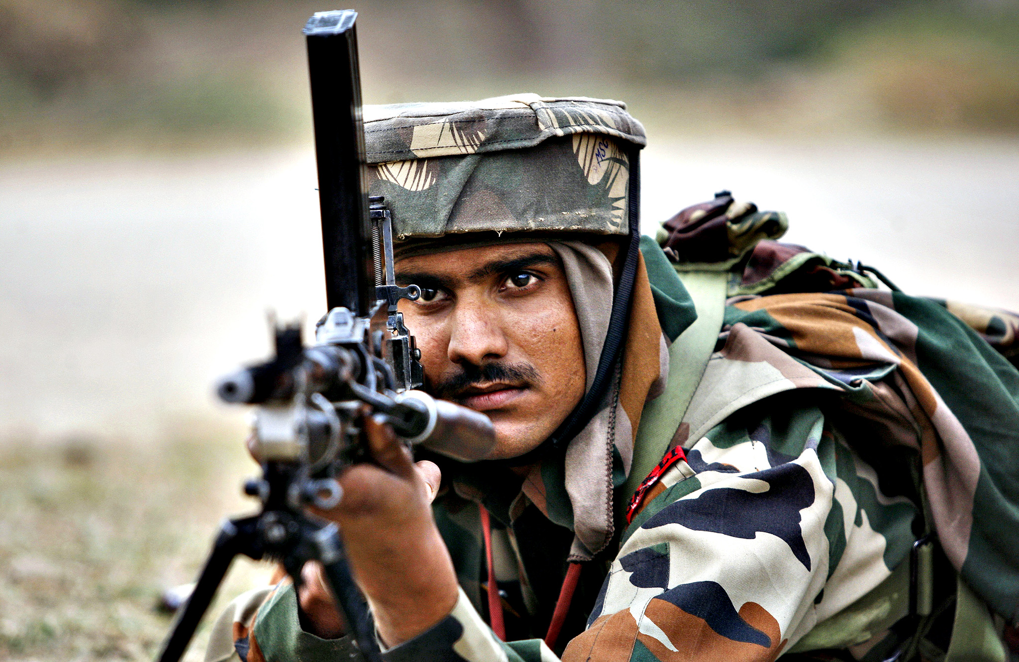 An Indian Army soldier takes position during an encounter with armed suspected militants at Pindi Khattar village in Arnia border sector, 43 kilometers (27 miles) south of Jammu, India, Thursday, Nov. 27, 2014. An army officer says some of the militants occupied an abandoned bunker in Jammu region early Thursday and fired at the soldiers in Arnia sector in the Indian portion of Kashmir.