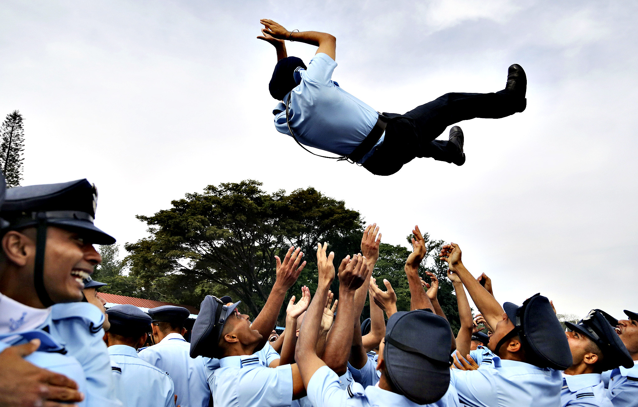 An Indian Air Force graduate is tossed in the air by his colleagues after their passing out parade ceremony in Bangalore, India, Friday, Nov. 28, 2014. A total of 121 officers including 45 women completed Friday after 74 weeks of training.