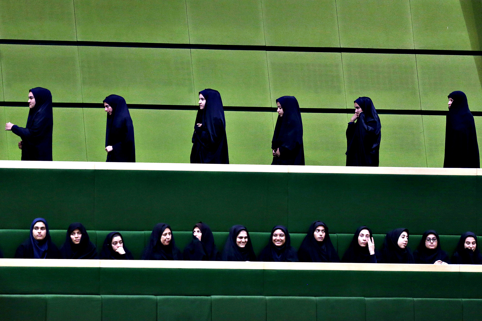 A group of female spectators leave as another group follows a debate of the Iranian parliament on a vote of confidence for nominee for the post of science minister Fakhroddin Ahamadi Danesh Ashtiani proposed by the President Hassan Rouhani, in Tehran, Iran, Tuesday, Nov. 18, 2014. Iran's parliament rejected Rouhani's nominee for the post of science minister over his pro-reform tendencies. In October the parliament rejected Mahmoud Nili Ahmadabadi, another nominee for the same post; the same body dismissed former-Science Minister Reza Faraji Dana in August over similar allegations.