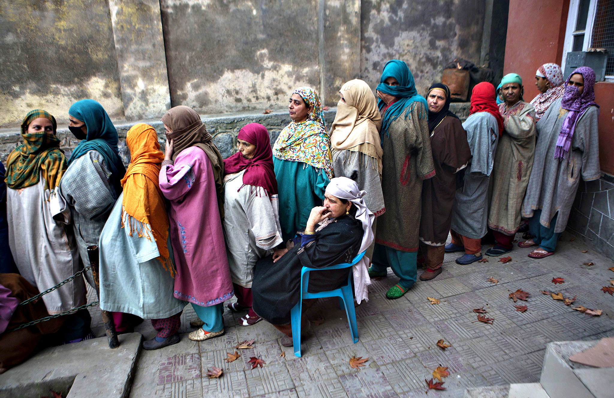 Kashmiri women wait in a queue to cast their votes during the first phase of polling to the Jammu and Kashmir state assembly elections in Lar, some 30 kilometers (19 miles) north of Srinagar, Indian controlled Kashmir, Tuesday, Nov. 25, 2014. The five phased voting is scheduled to be held till December 20 with the results expected on December 23.