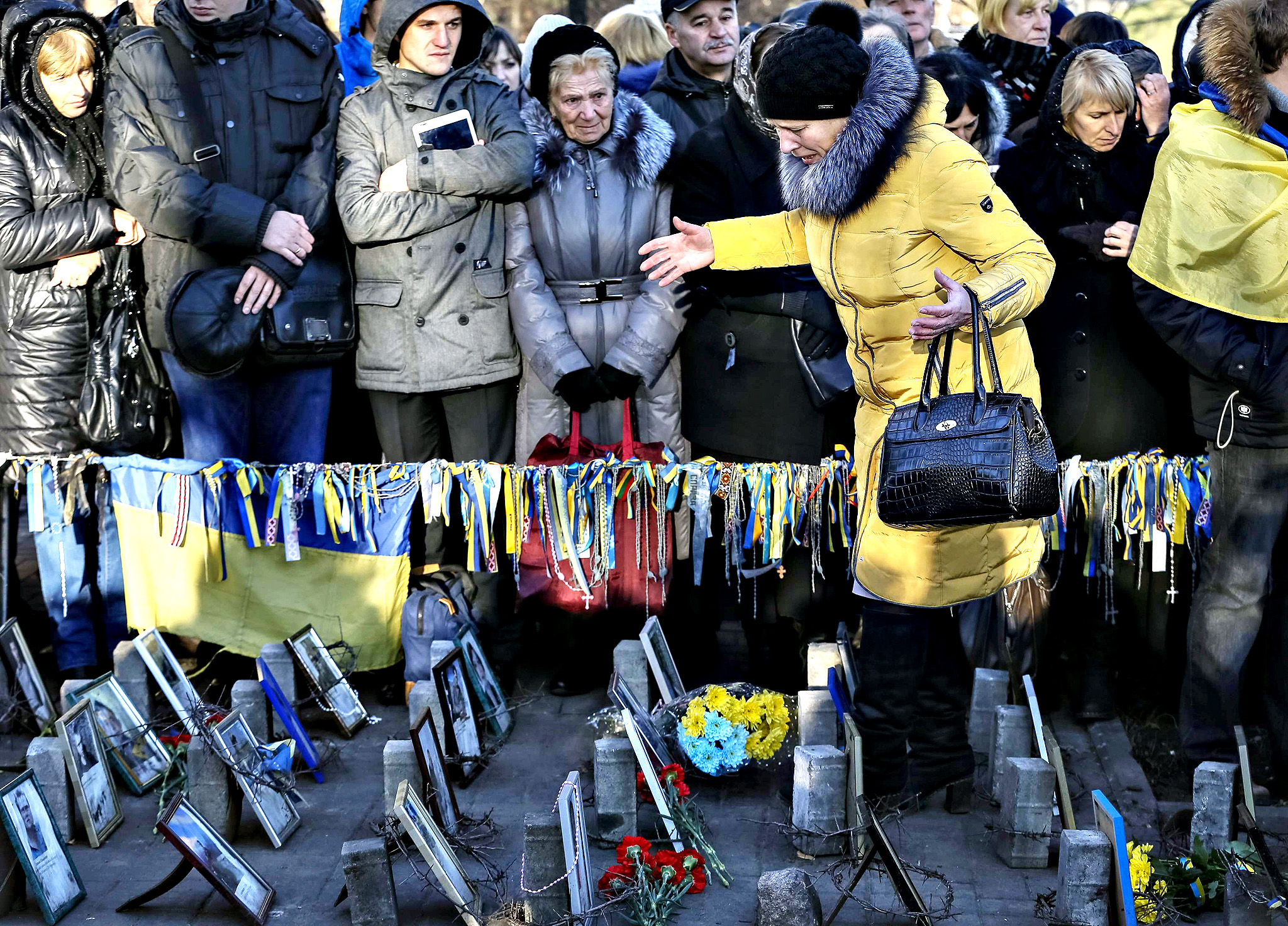 A woman reacts as she walks in between photos of anti-Yanukovich protesters killed during clashes, during a commemoration ceremony for them in Kiev...A woman reacts as she walks in between photos of anti-Yanukovich protesters killed during clashes, during a commemoration ceremony for them in Kiev November 21, 2014. Ukrainians marked the first anniversary of Ukrainian pro-European Union (EU) mass protests which caused a change in the country's leadership and brought Ukraine closer to the EU.
