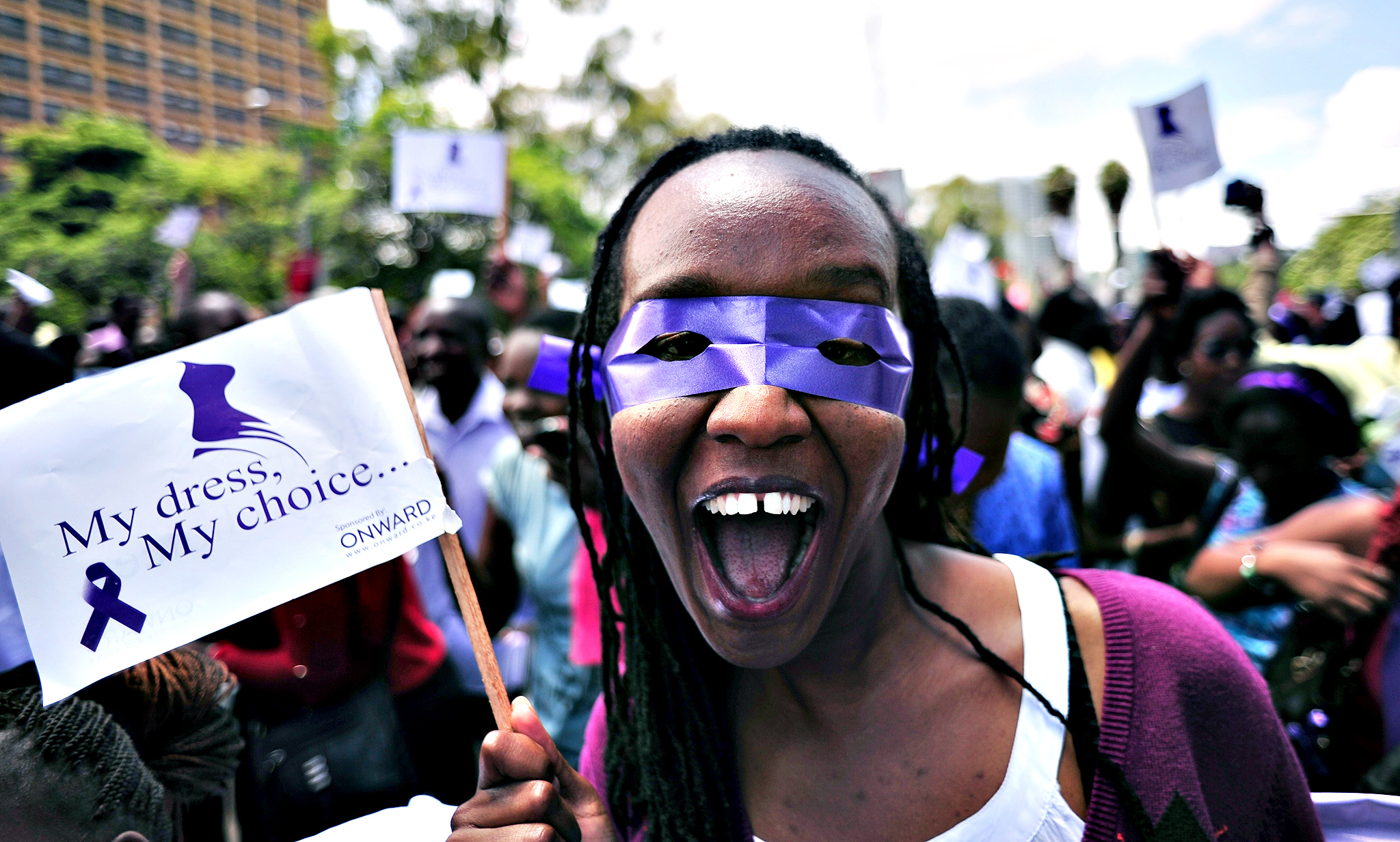 "A woman takes part in a rally to protest against violence towards women, on November 17, 2014 in the Kenyan capital, Nairobi. Some 200 women gathered to rally in support of a woman who was attacked and stripped last week by a mob at a bus stop,  in an incident that was captured on video and went viral online. She was accused of ""tempting"" men because of her clothing."