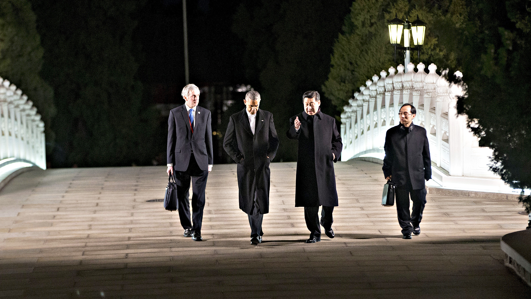 U.S. President Barack Obama, second left, and Chinese President Xi Jinping, second right, walk together at Zhongnanhai leaders compound before their private dinner, Tuesday, Nov. 11, 2014. The others walking with them are their translators.