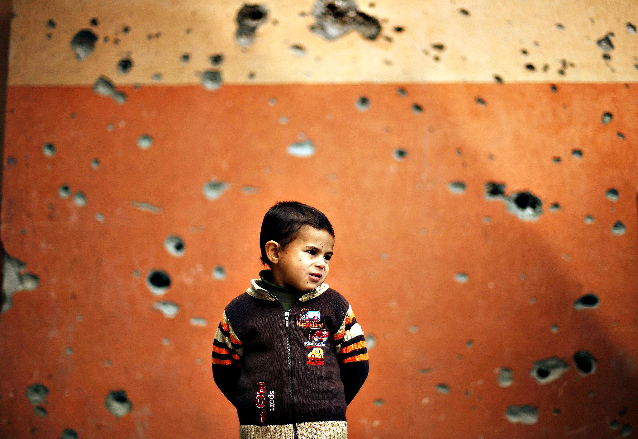 A Palestinian boy stands outside a mosque, that witnesses said was damaged by Israeli shelling during the most recent conflict between Israel and Hamas, on a winter day in Beit Hanoun town, northern Gaza Strip, November 25, 2014.