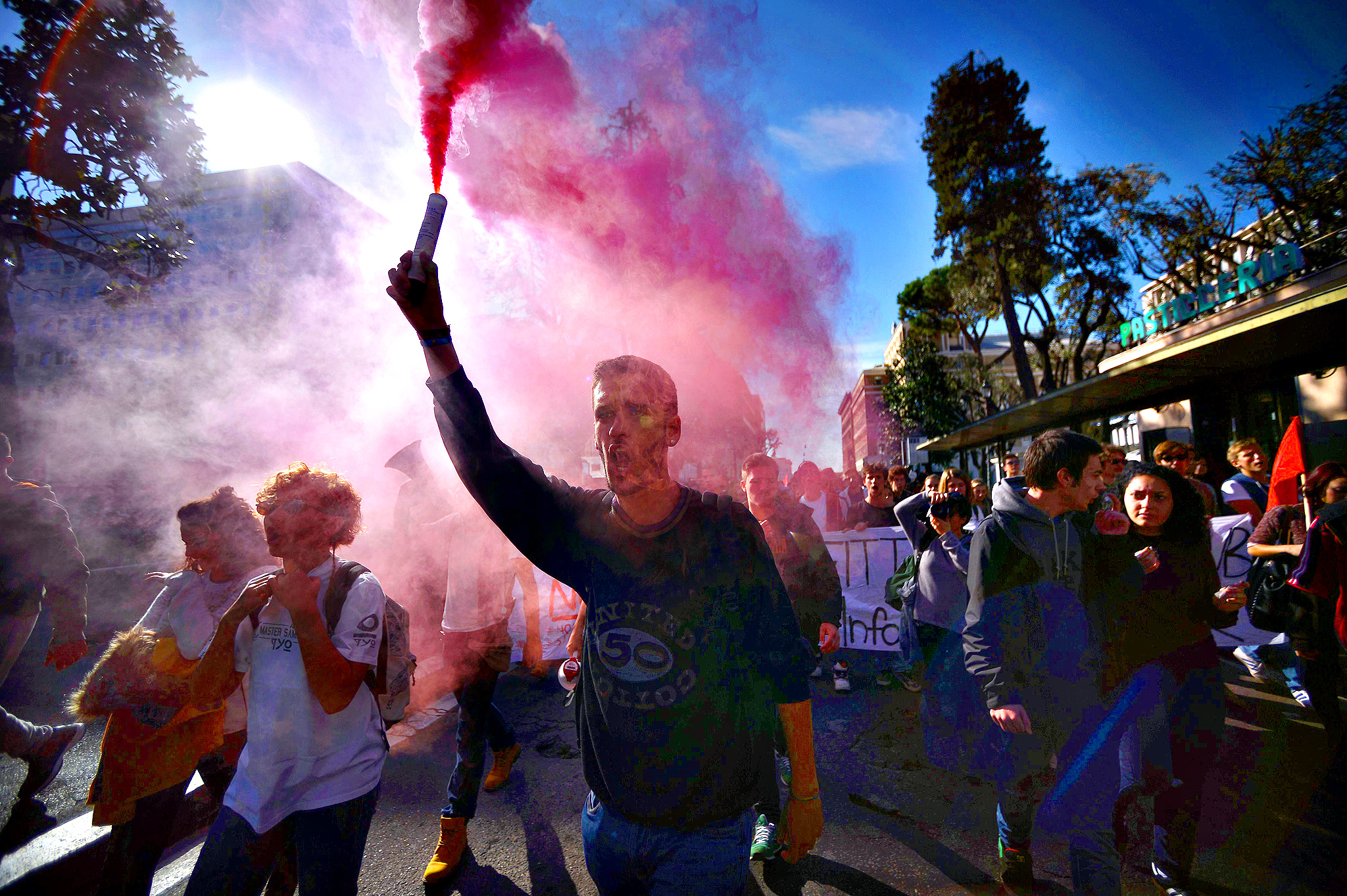 Demonstators hold flares during a demonstration as part of a general strike in central Rome on November 14, 2014.